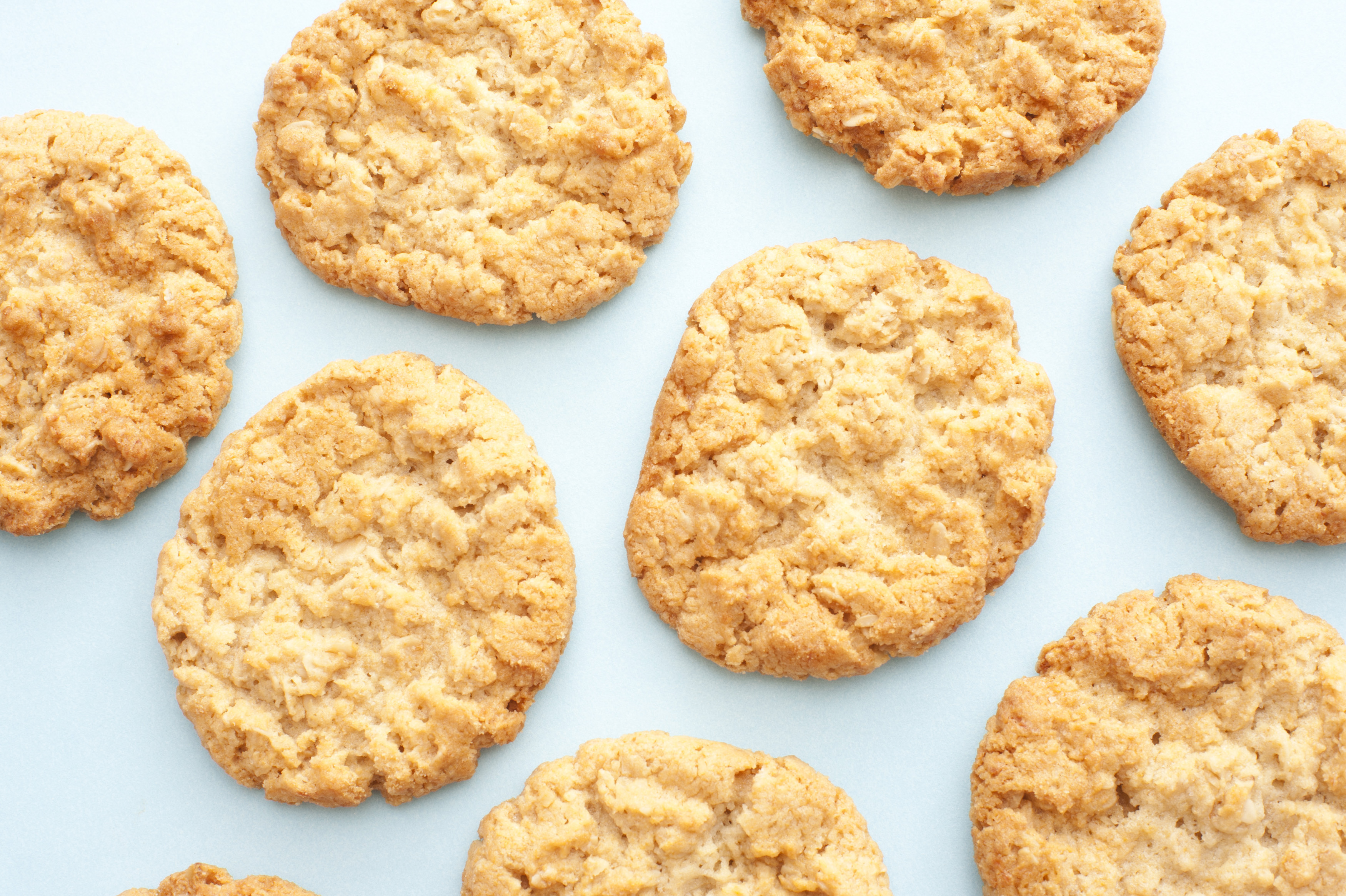 Background of fresh golden oatmeal cookies scattered on a white surface viewed from overhead in a full frame view