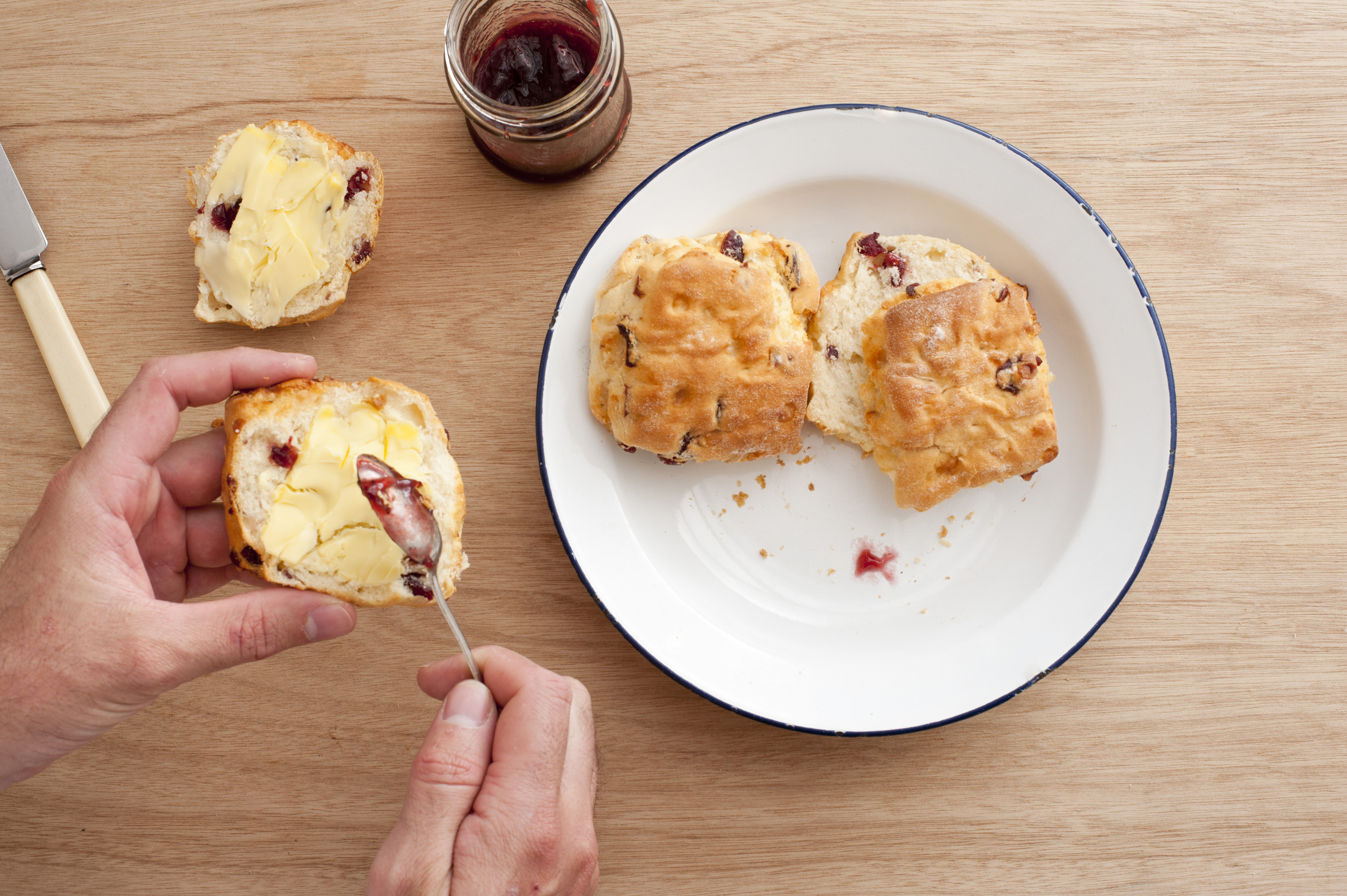 First person perspective view on pair of male hands applying jam on scones next to plate over table
