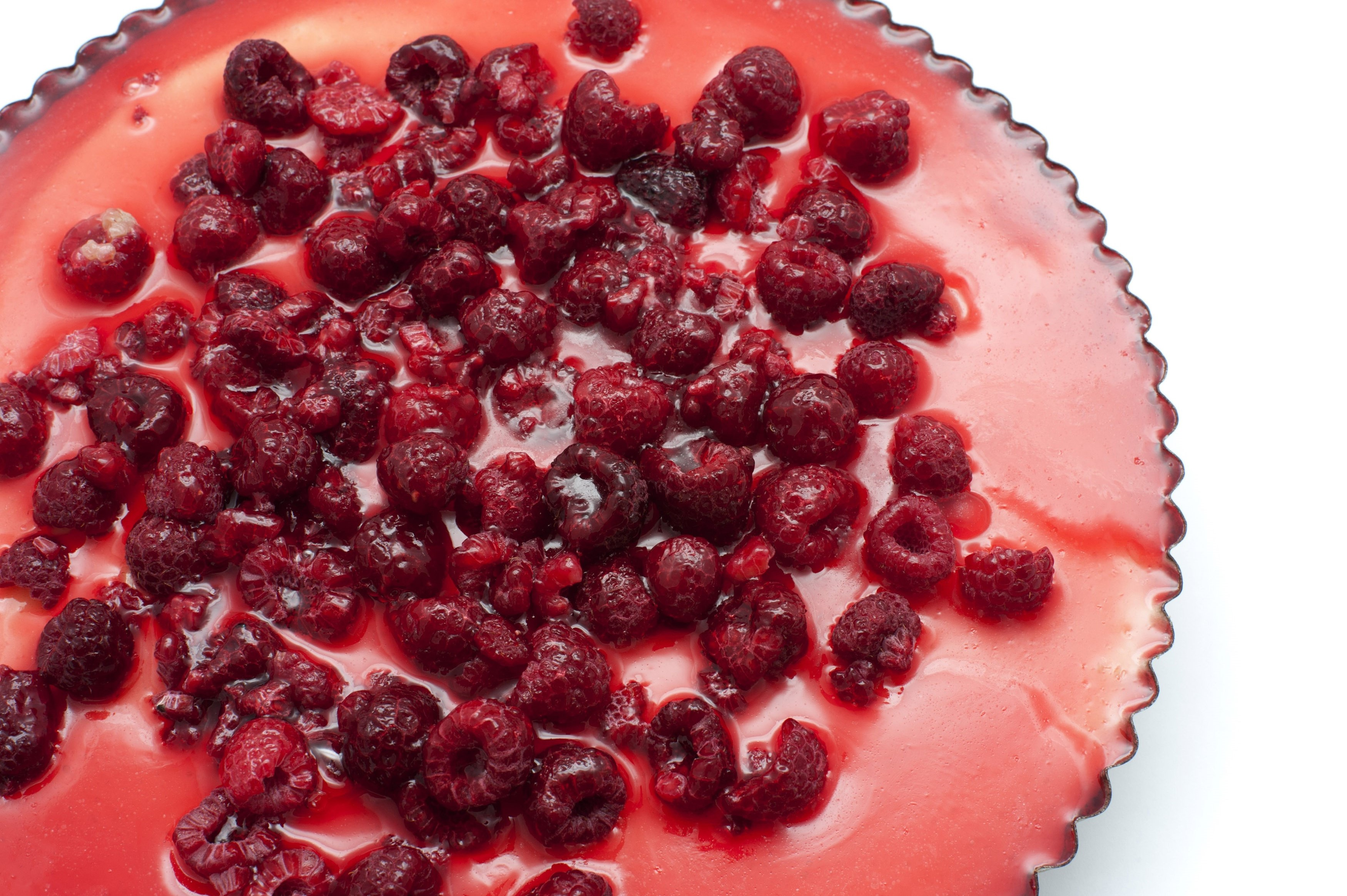 View from above of a freshly baked cheesecake in a fluted pan topped with tasty raspberries for a gourmet dessert