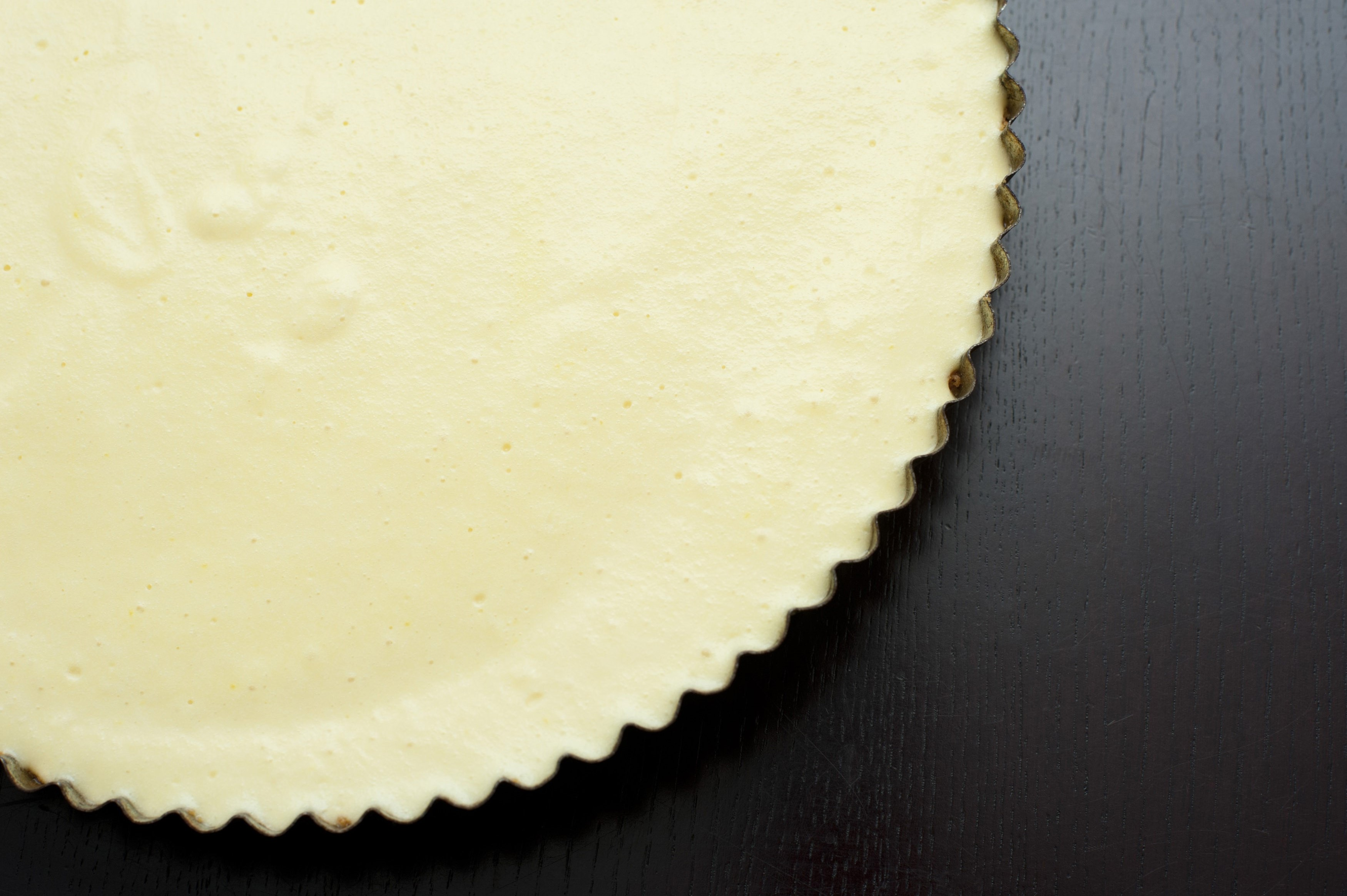 Overhead view of a plain baked cheesecake in a fluted metal pan over a dark background with copyspace