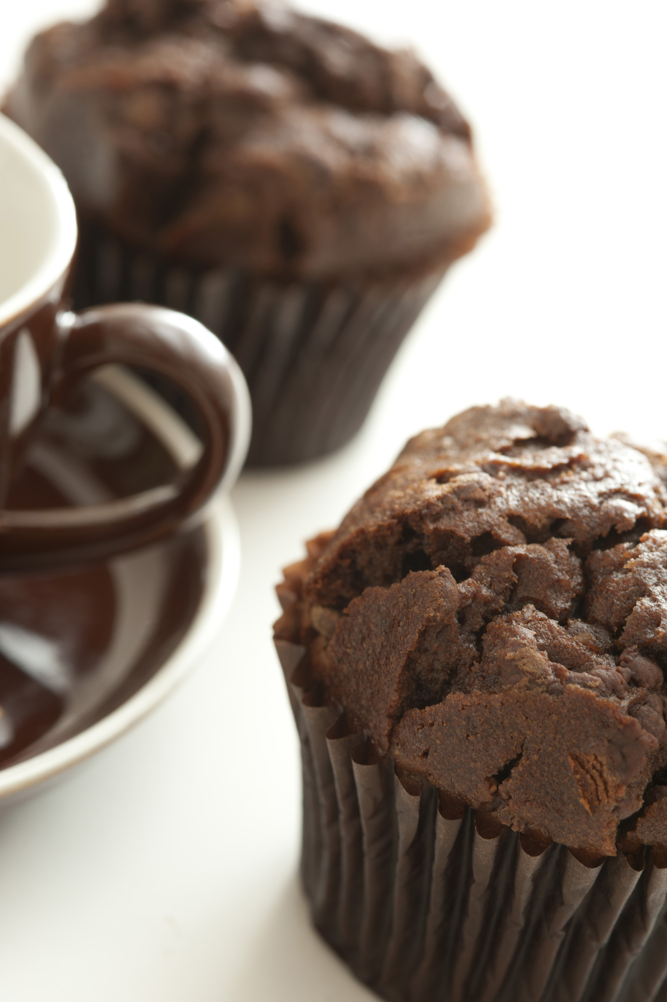 Pair of freshly baked large chocolate muffin desserts beside brown coffee cup and saucer