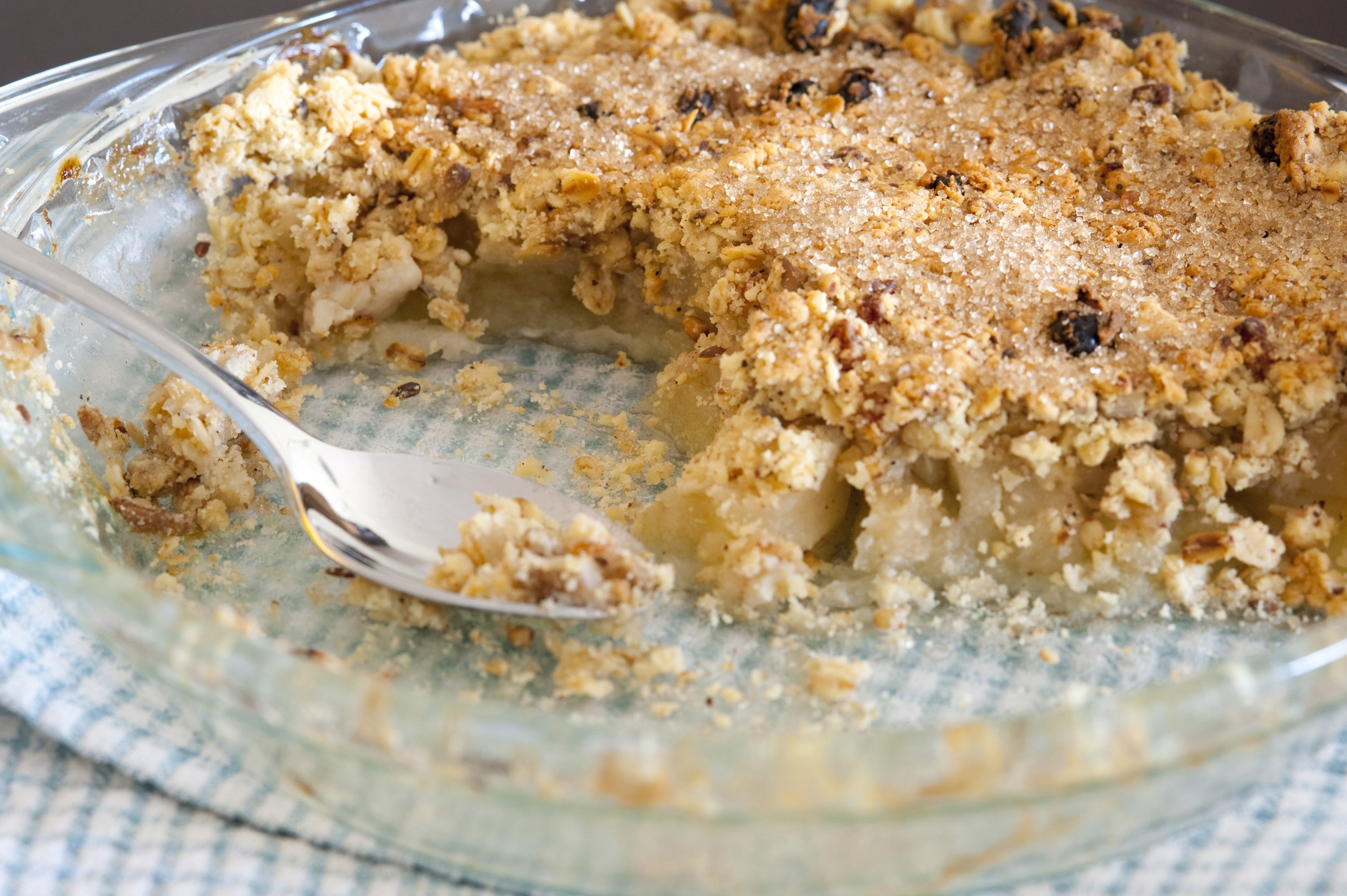 Freshly baked apple crumble dessert topped with spicy crumble with raisins in a glass pie plate