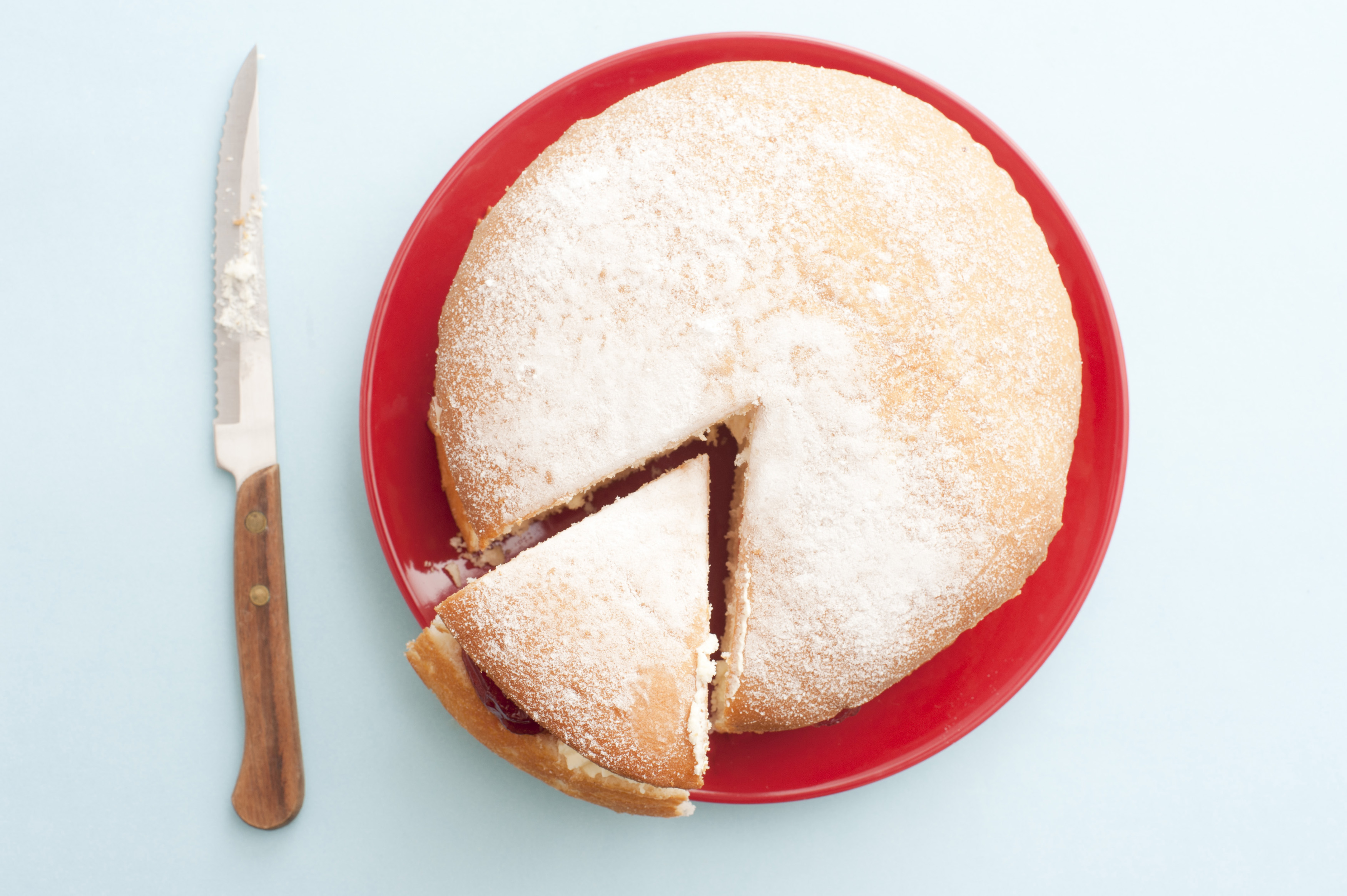 Top down view recently sliced wedge of delicious cake over round red plate next to cutting knife over table