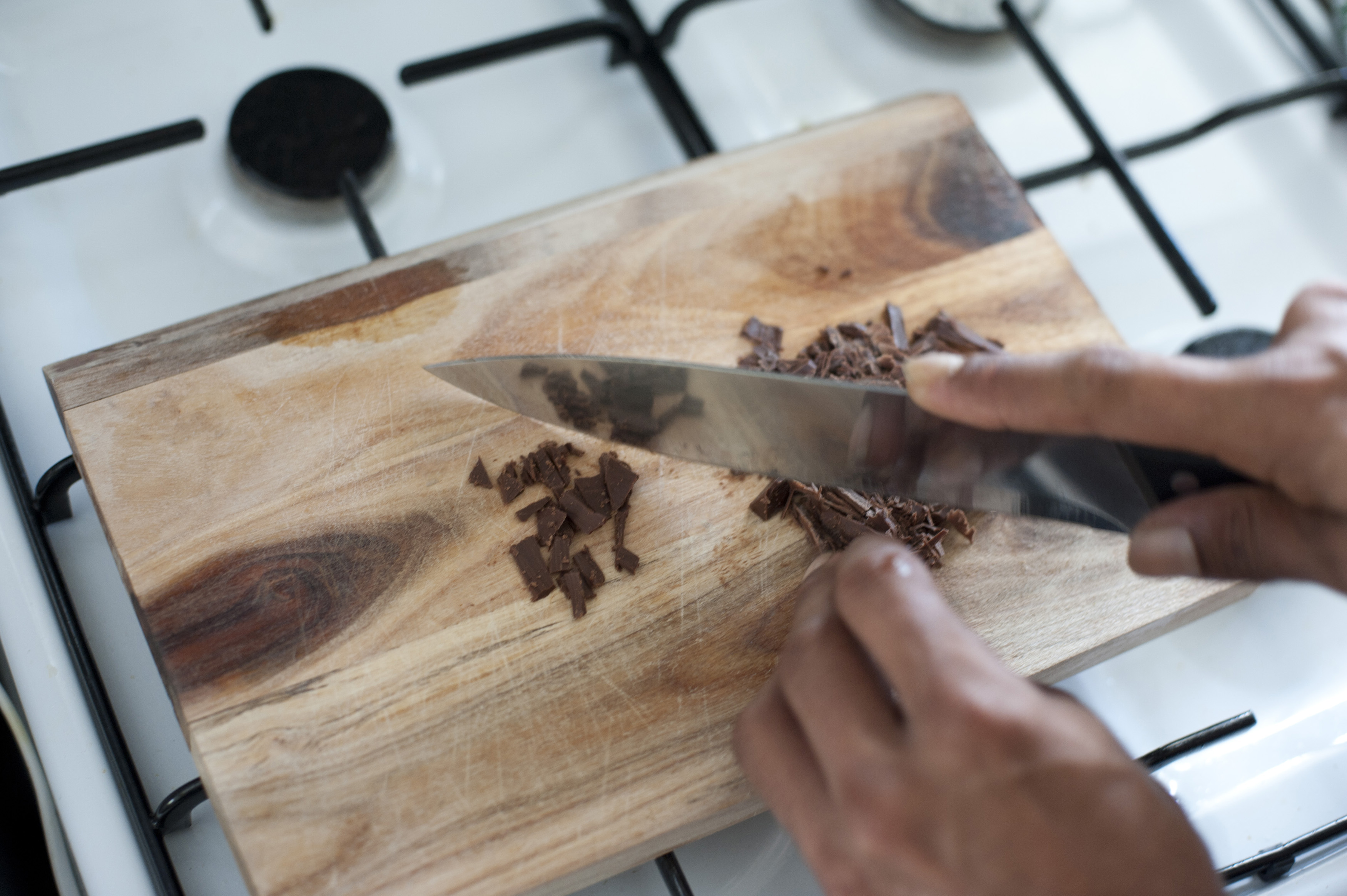 Close up view of the hands of a male chef or cook chopping chocolate for baking on a wooden cutting board on a gas hob
