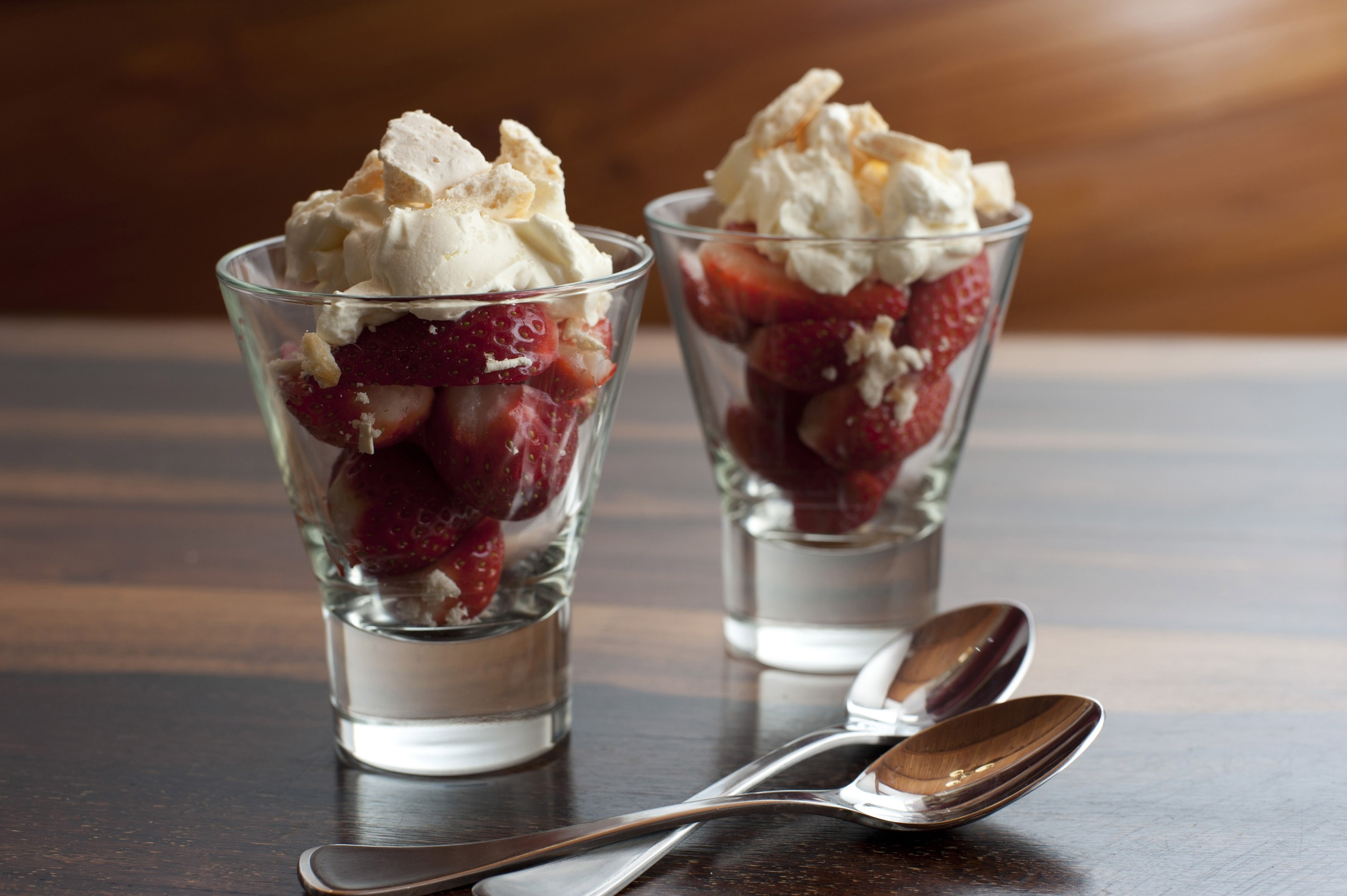 Fresh ripe red strawberry and cream dessert served in glasses and standing on a wooden counter top with two spoons
