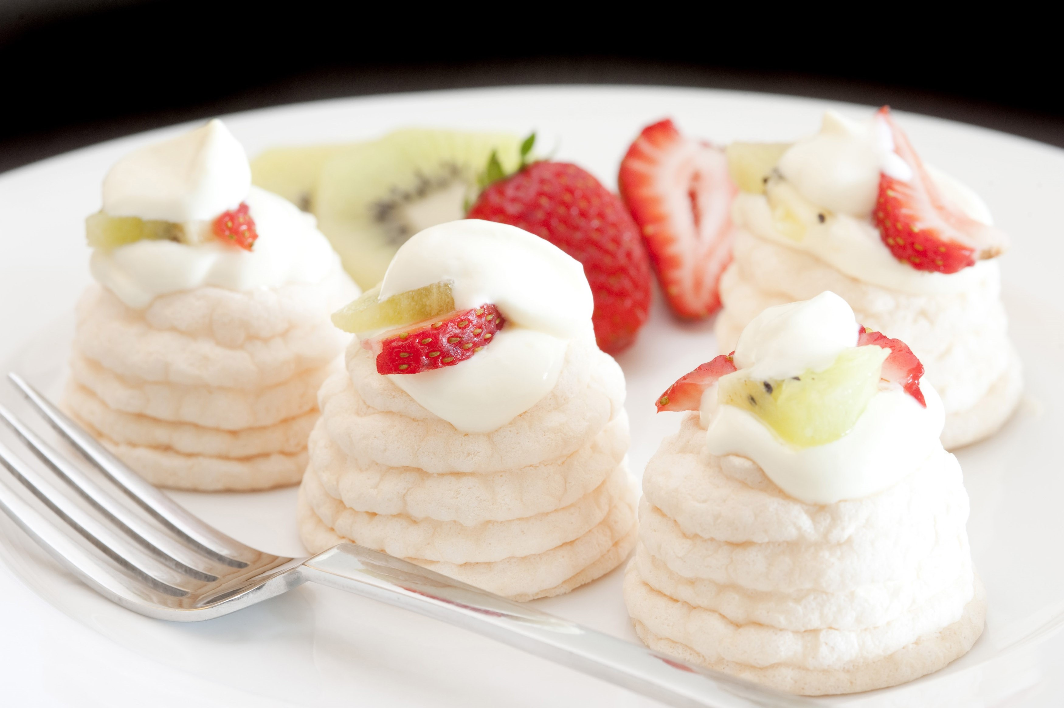 Individual meringue cases filled with whipped cream and topped with sliced fresh fruit including strawberries and kiwi fruit