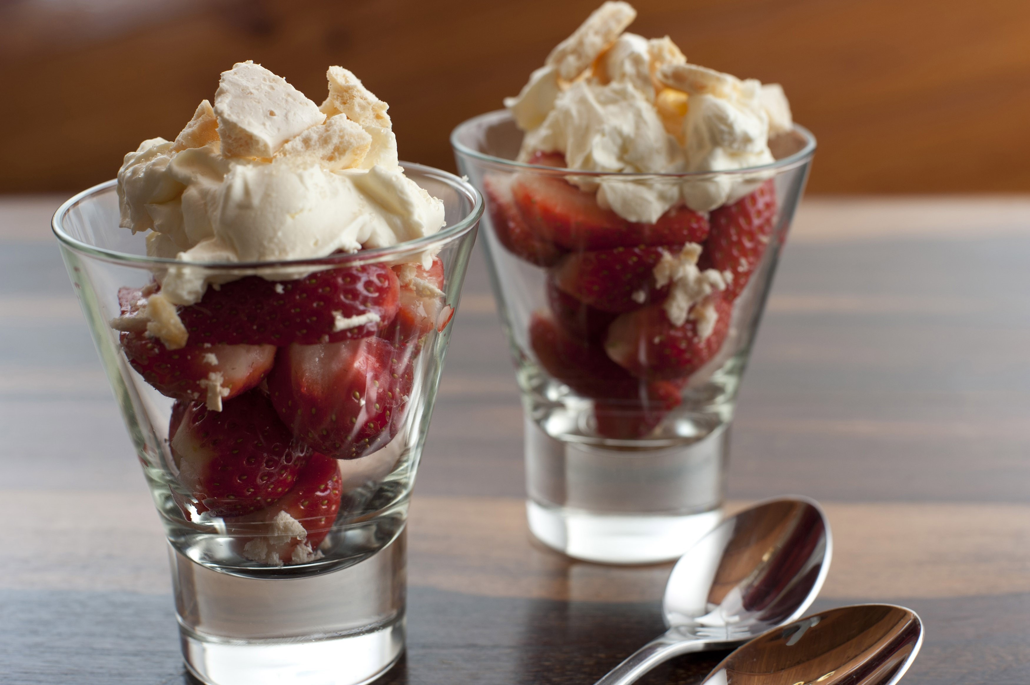Strawberries and whipped cream dessert in two tall glasses for a delicious fruity sweet