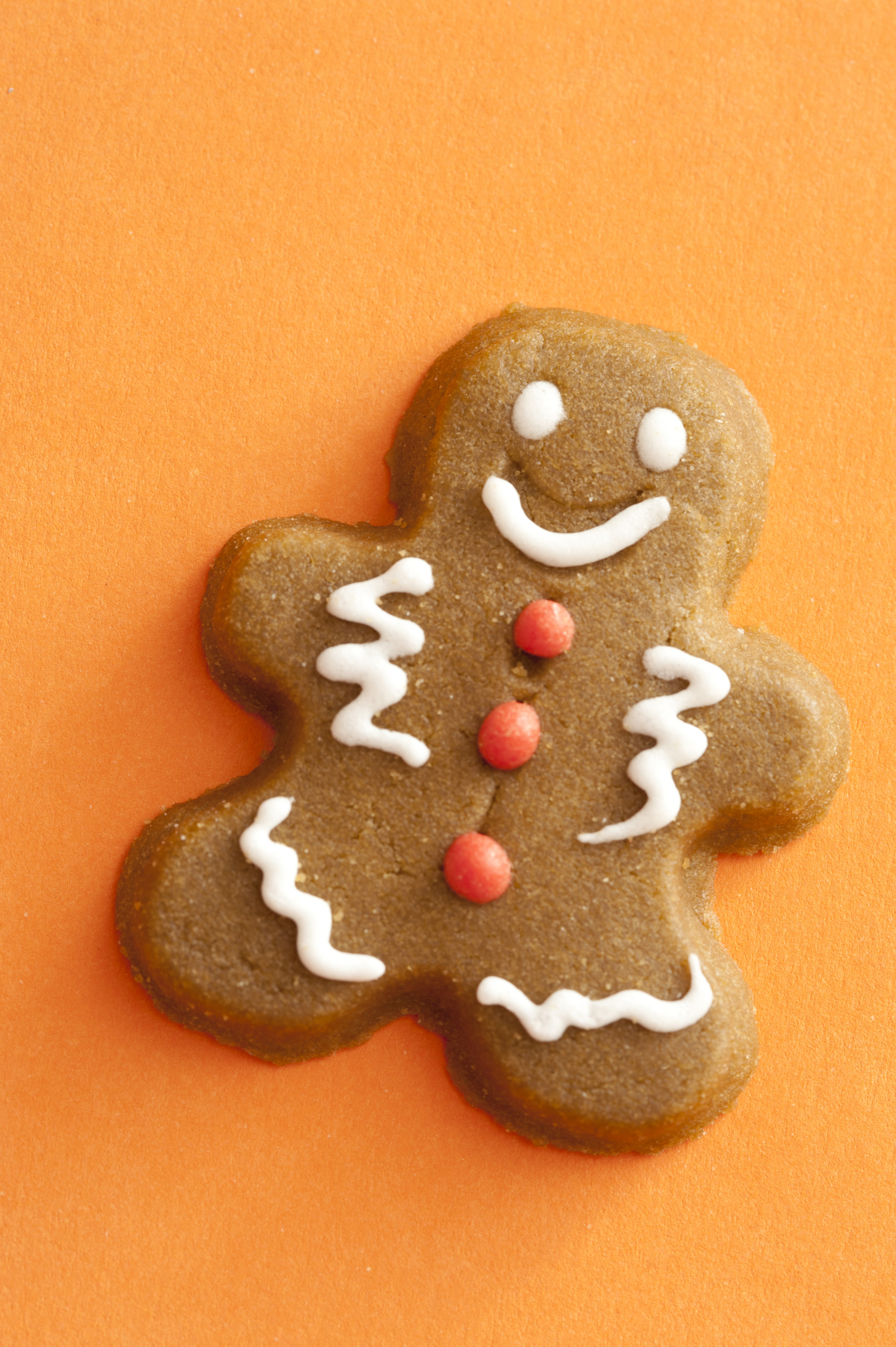 Gingerbread man or cookie decorated with icing on a festive orange background with copy space, overhead view