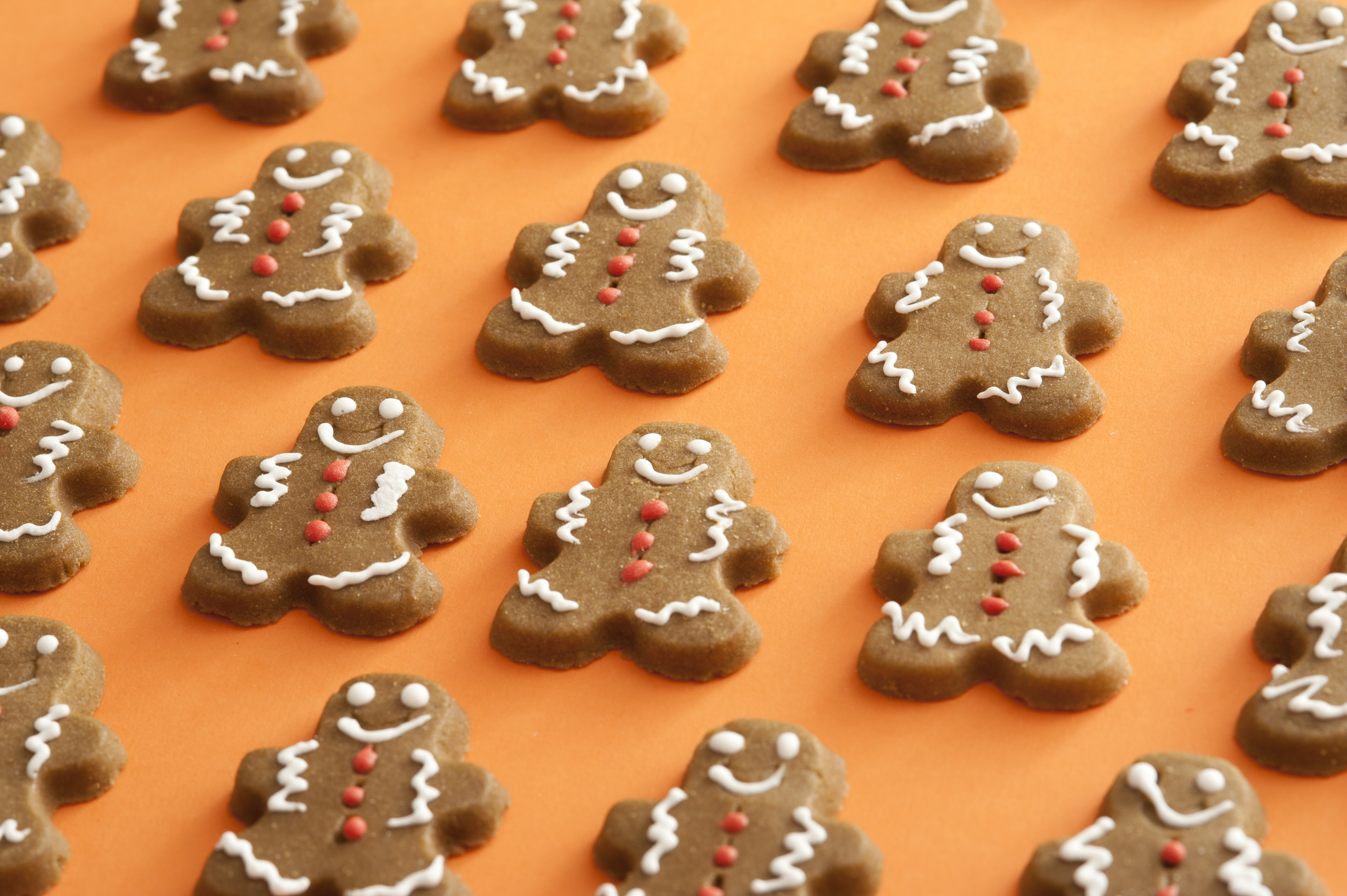 Endless rows of delicious brown icing decorated gingerbread man sweet cookies over orange background