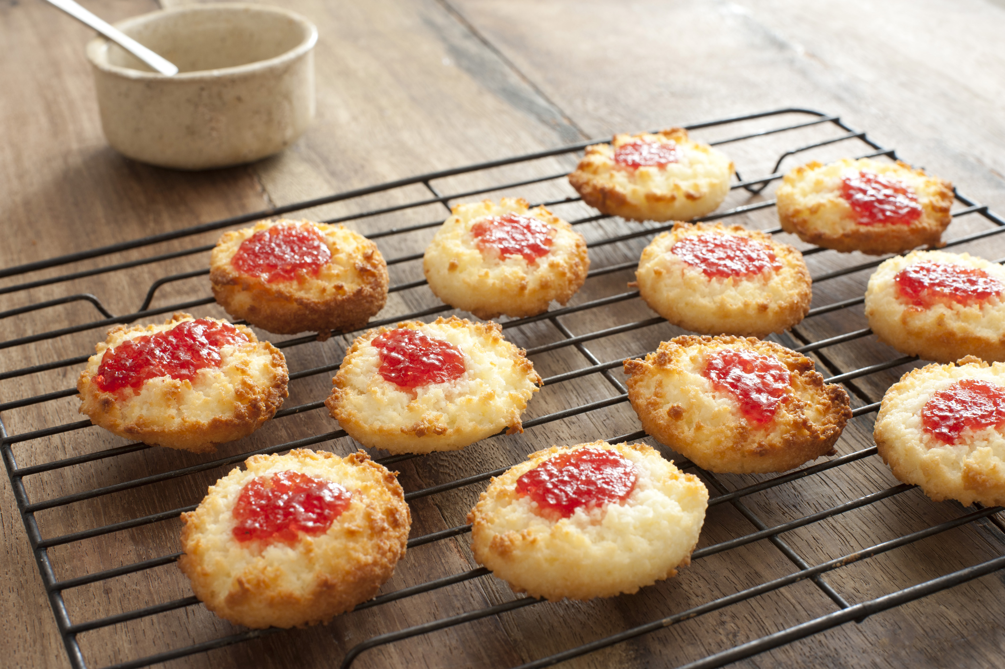 Oven tray full of baked coconut cookies with strawberry jam in the middle over table next to dish