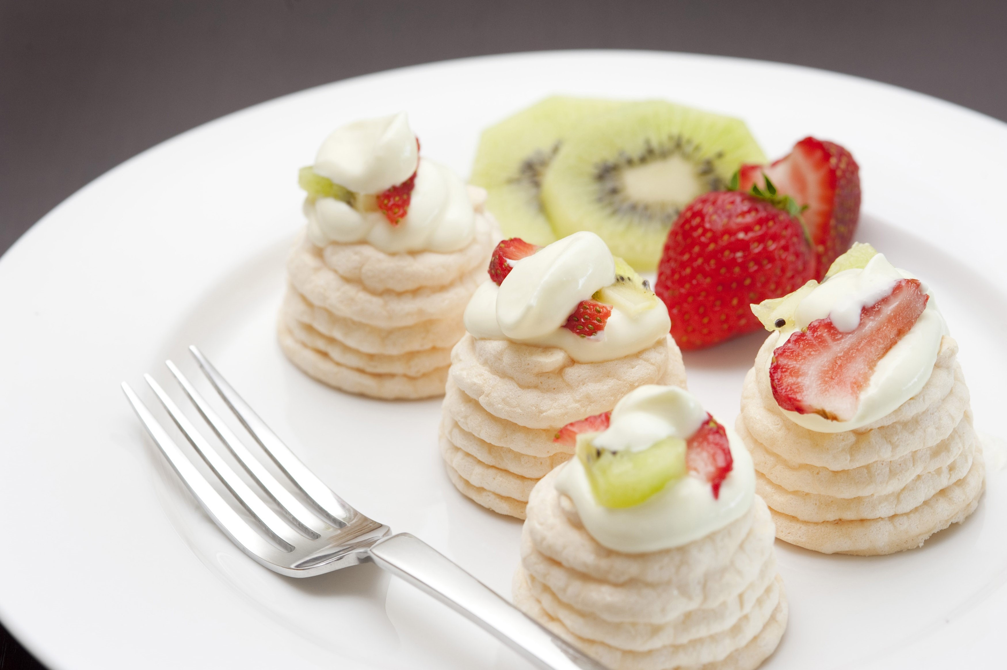 Meringue dessert with small individual meringues filled with cream and topped with kiwi fruit and strawberries