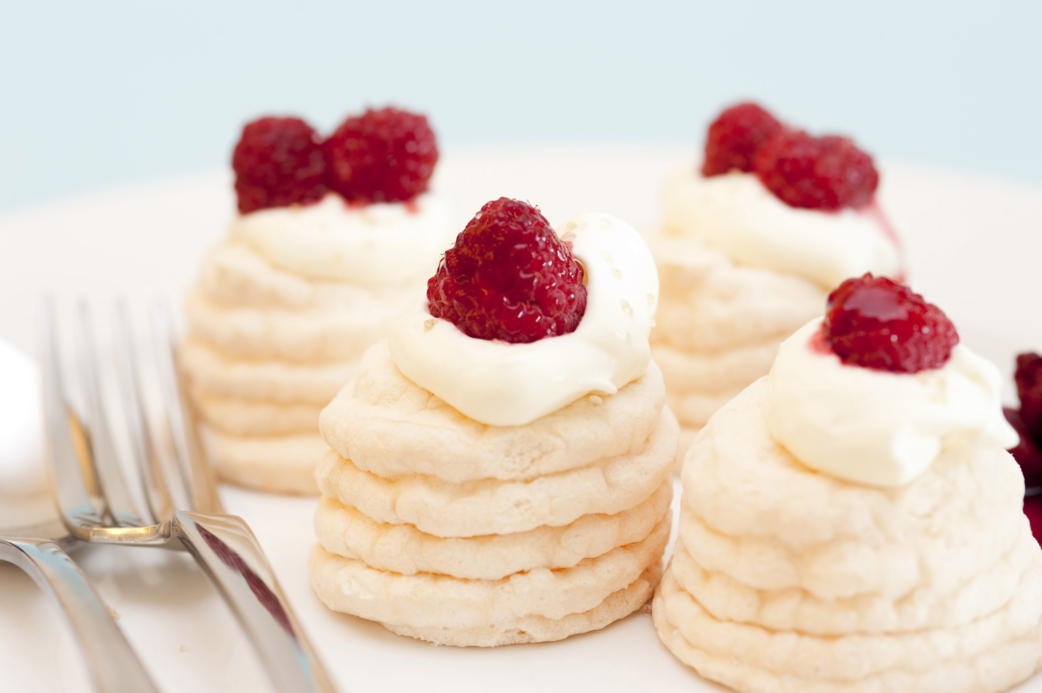 Decorative twirled cone meringues filled with fresh whipped cream and topped with ripe red strawberries