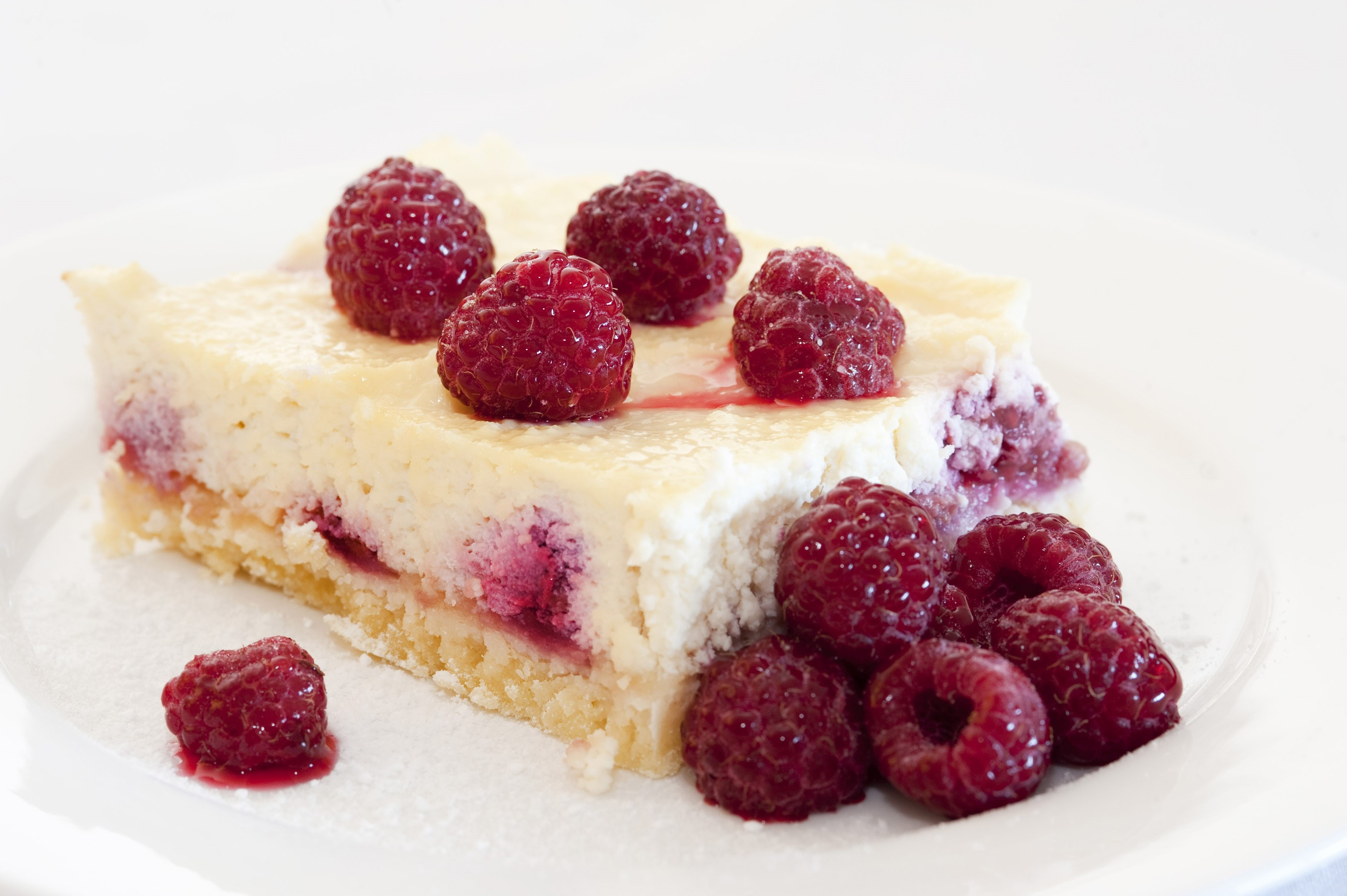 Slice of freshly baked ricotta cheesecake with raspberries served on a plate over a white background