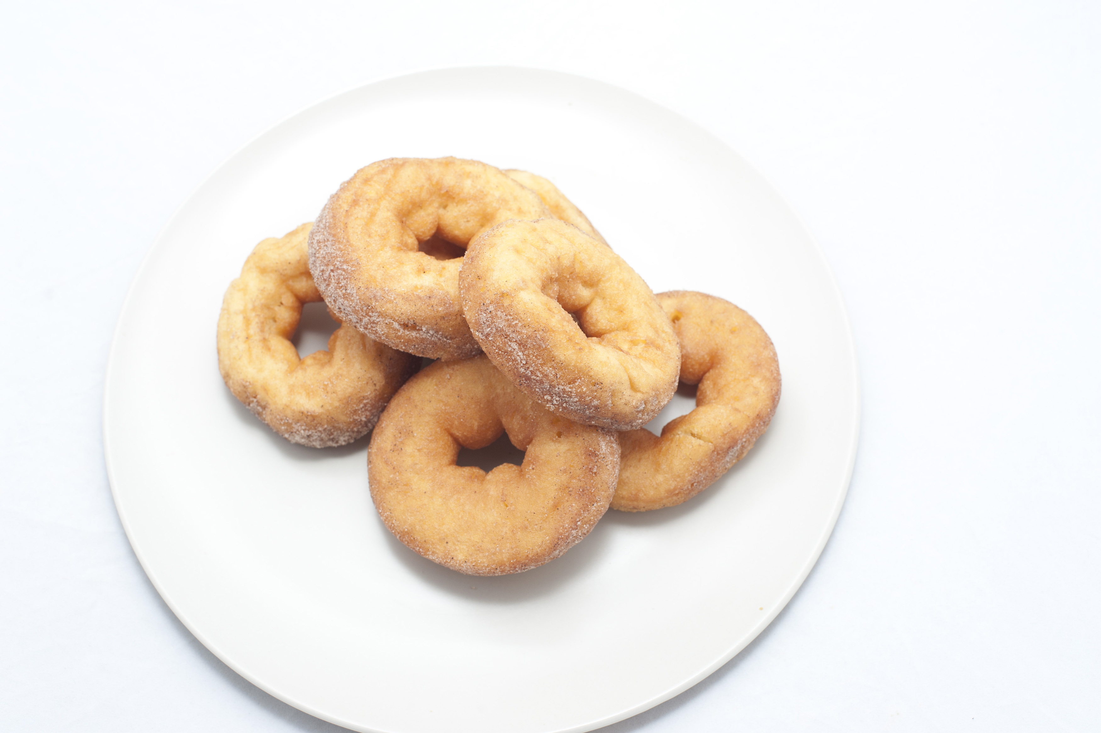 Plate of five sweet plain ring doughnuts for a tasty but unhealthy snack or breakfast viewed high angle on white