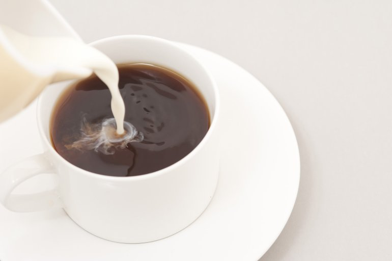 Pouring milk into a cup of coffee - Free Stock Image