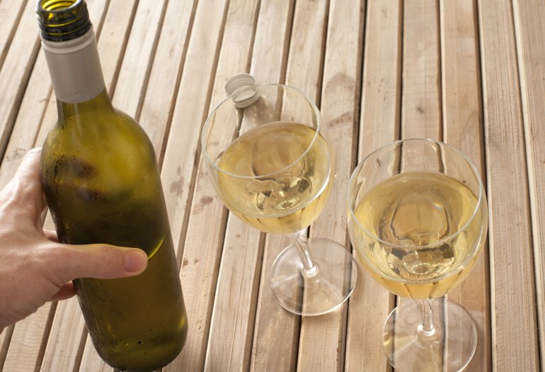 Man pouring white wine into two glasses - Free Stock Image