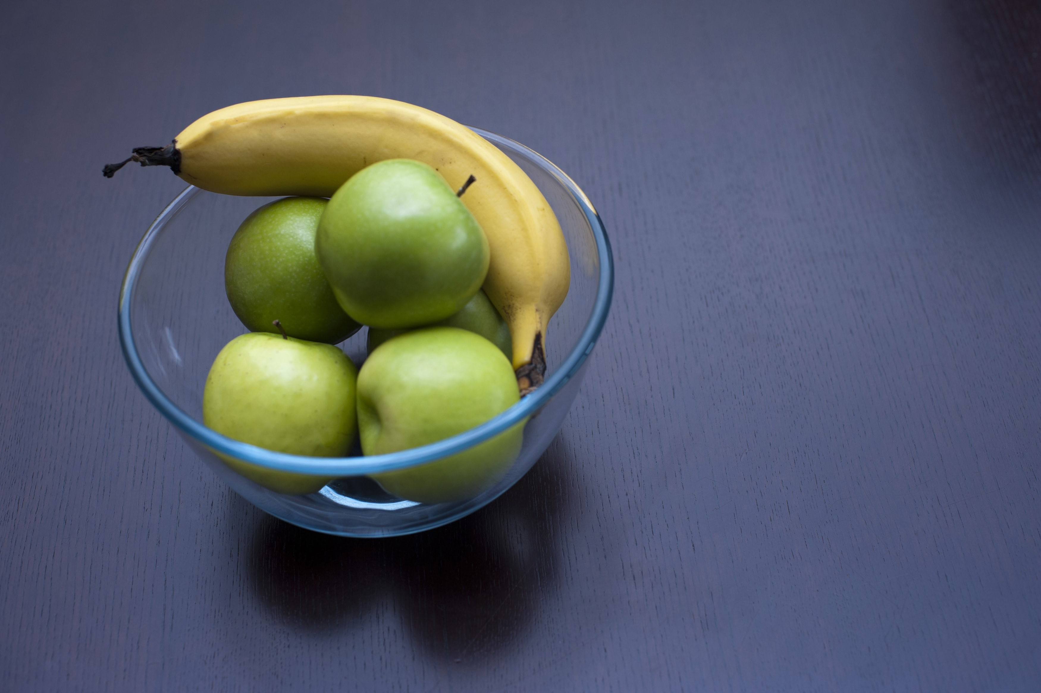 Crisp green apples and a ripe banana in a glass bowl for a healthy nutritional snack, high angle view on a blue background with copyspace