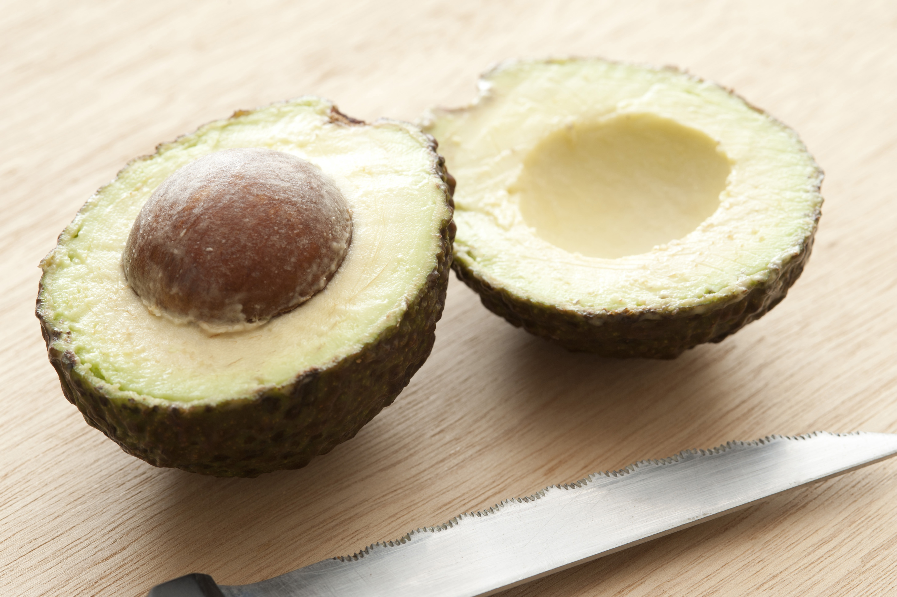 Close-up of cut fresh avocado and knife on wooden table