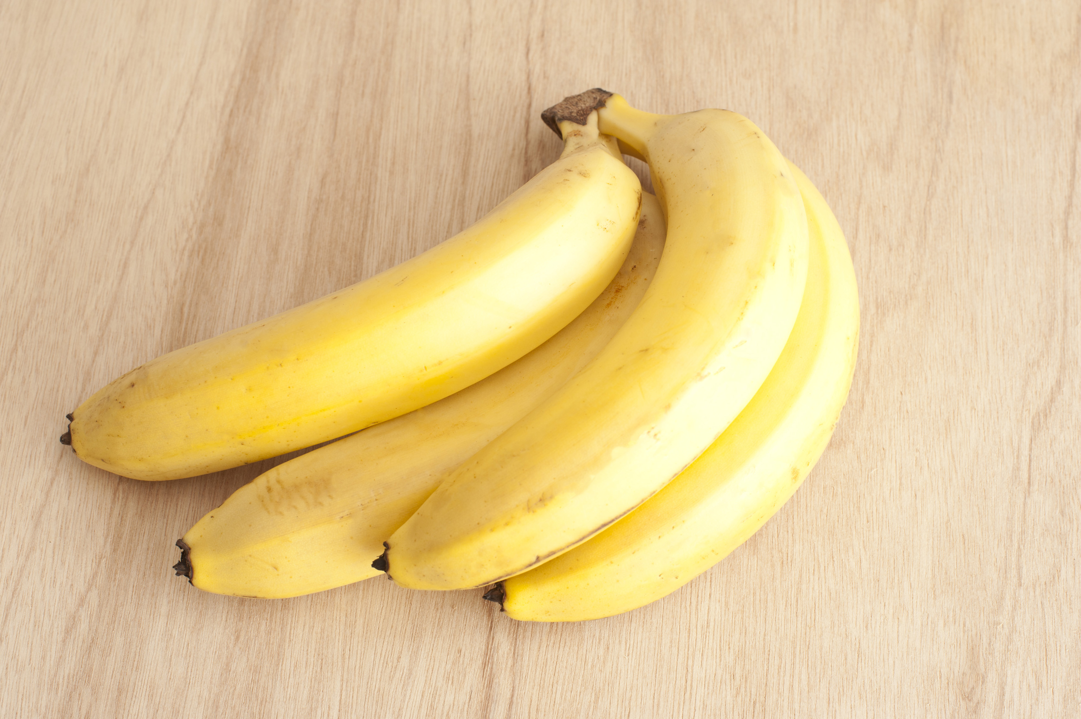 High Angle Close Up Still Life of Bunch of Four Ripe Yellow Bananas on Wooden Background
