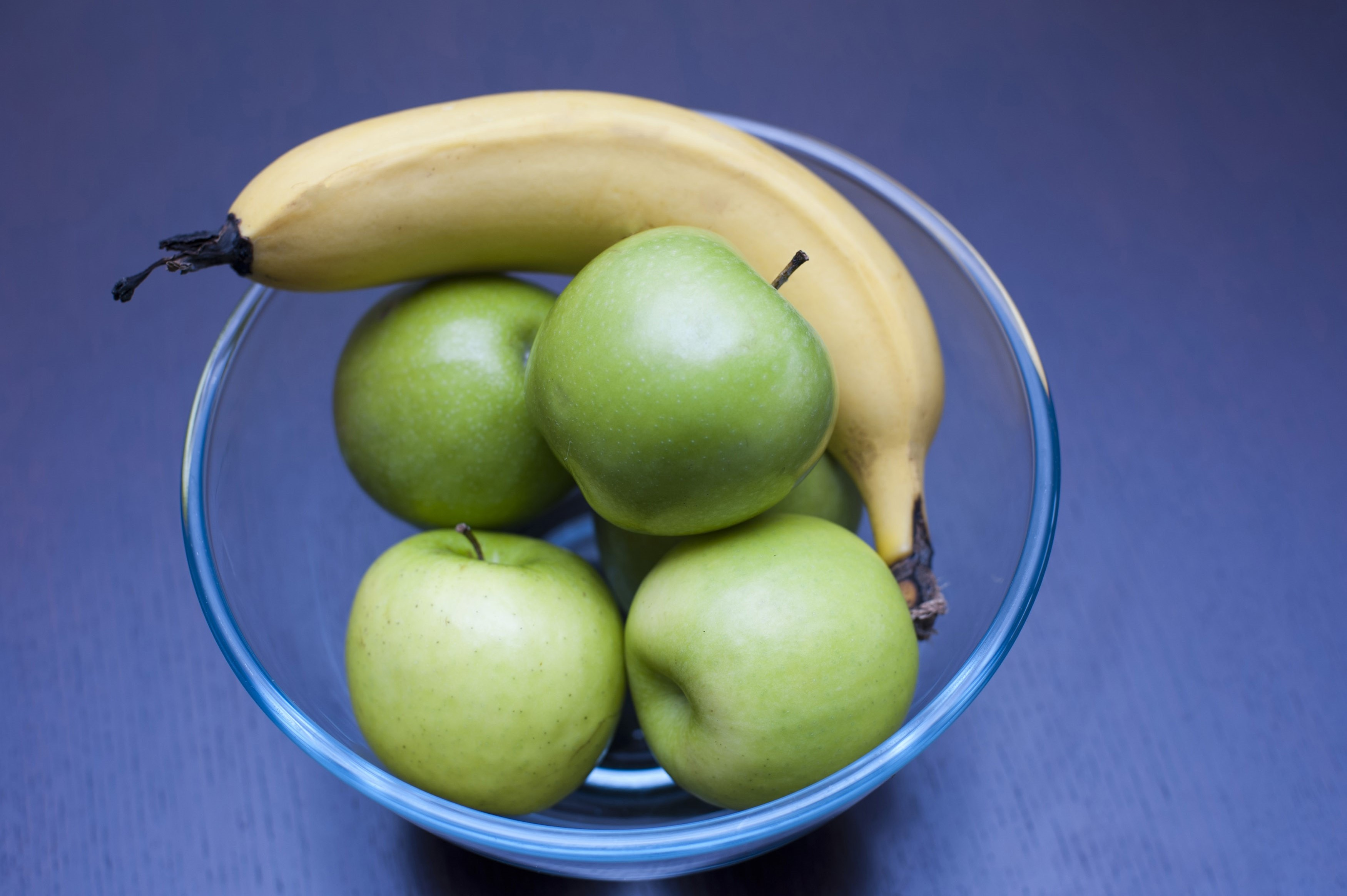 High angle view of a clear glass bowl with fresh healthy green apples and a banana to be eaten as a snack on a blue background