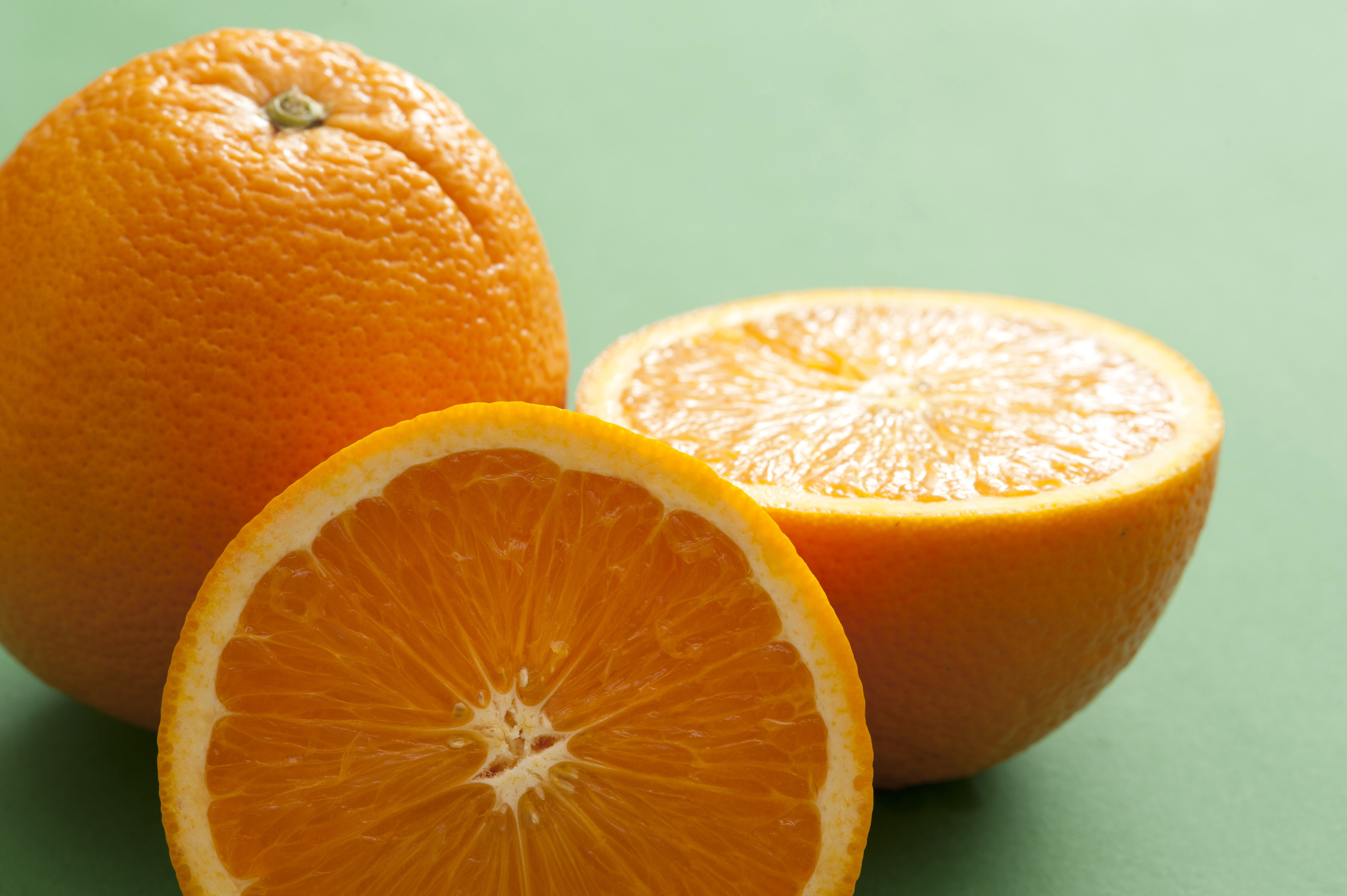 Close-up of one whole and cut orange on green background