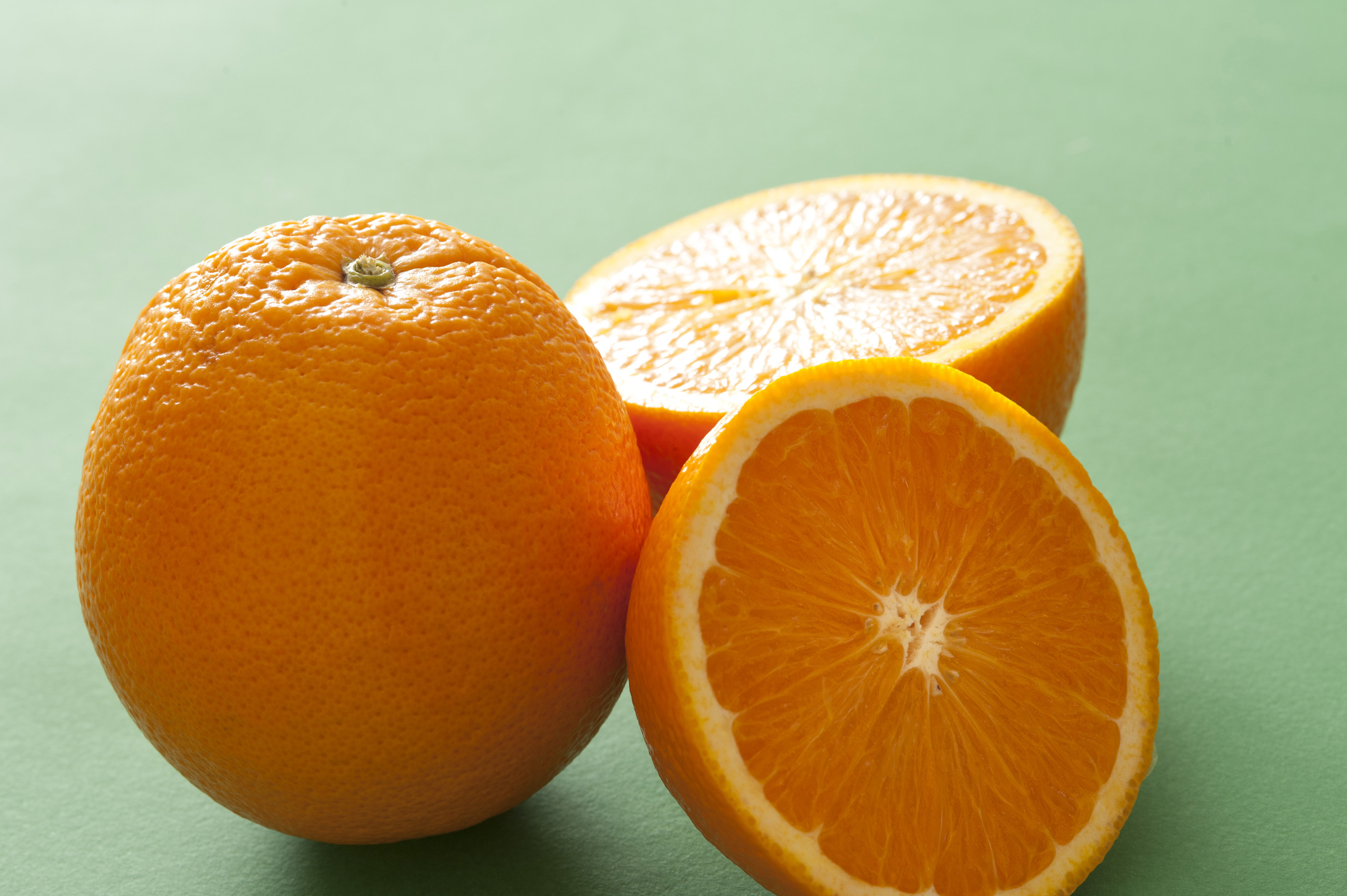 Still life of one whole orange and two halves of cut orange on green background