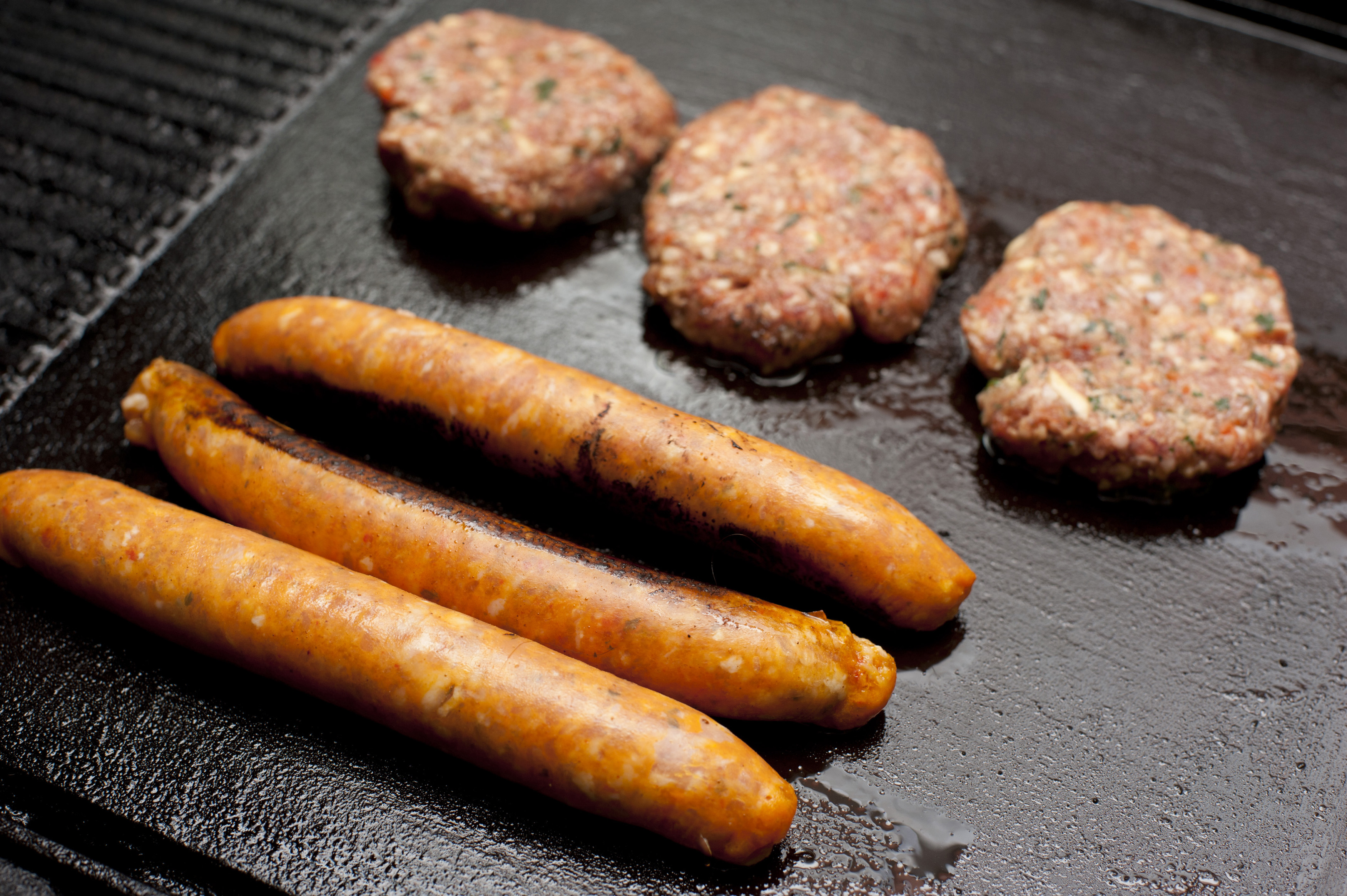 Raw meat rissoles and sausages on grill