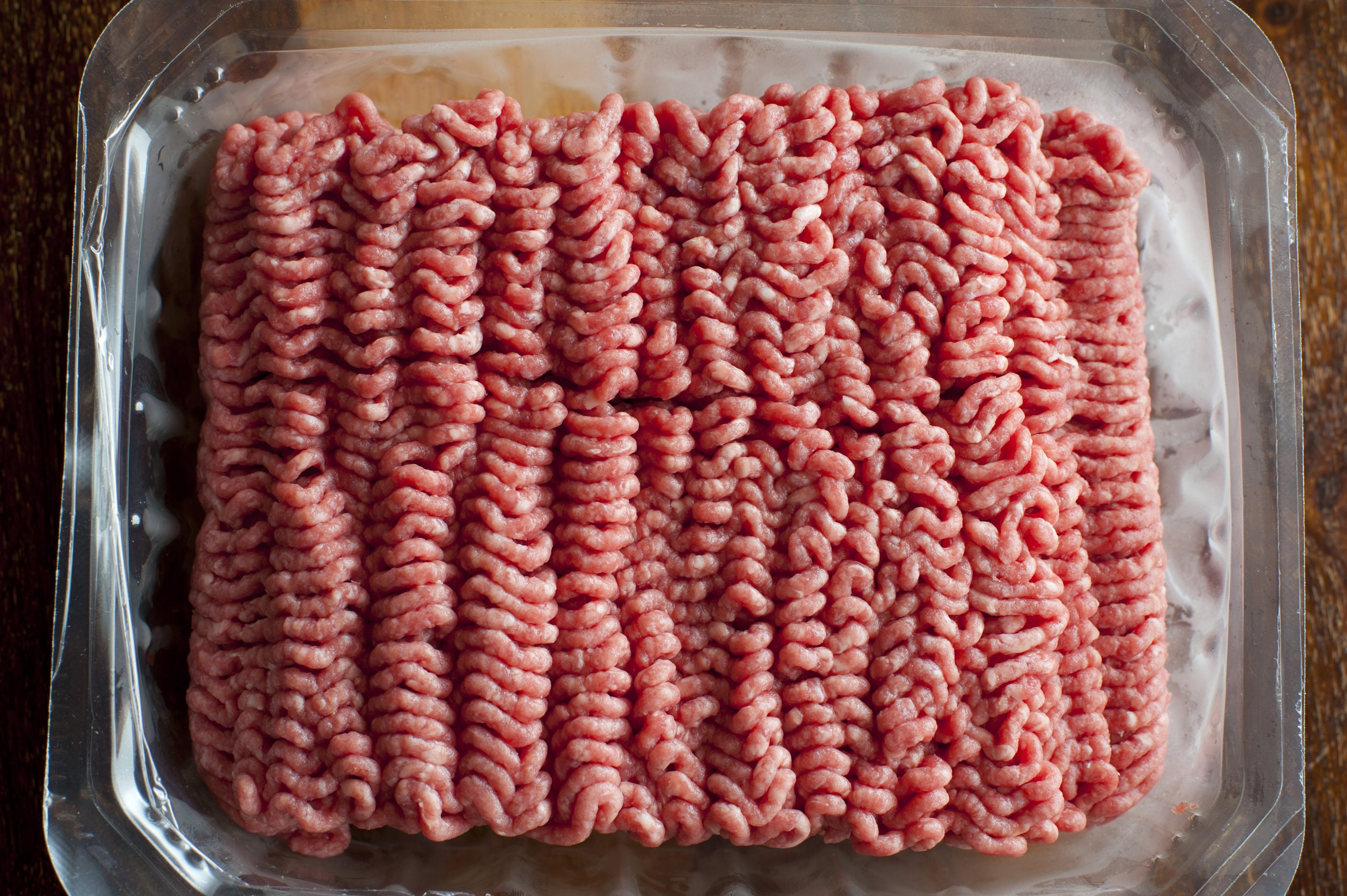 Punnet of raw beef mince arranged in lines from the mincing machine at the butchery and a healthy ingredient in everyday cooking