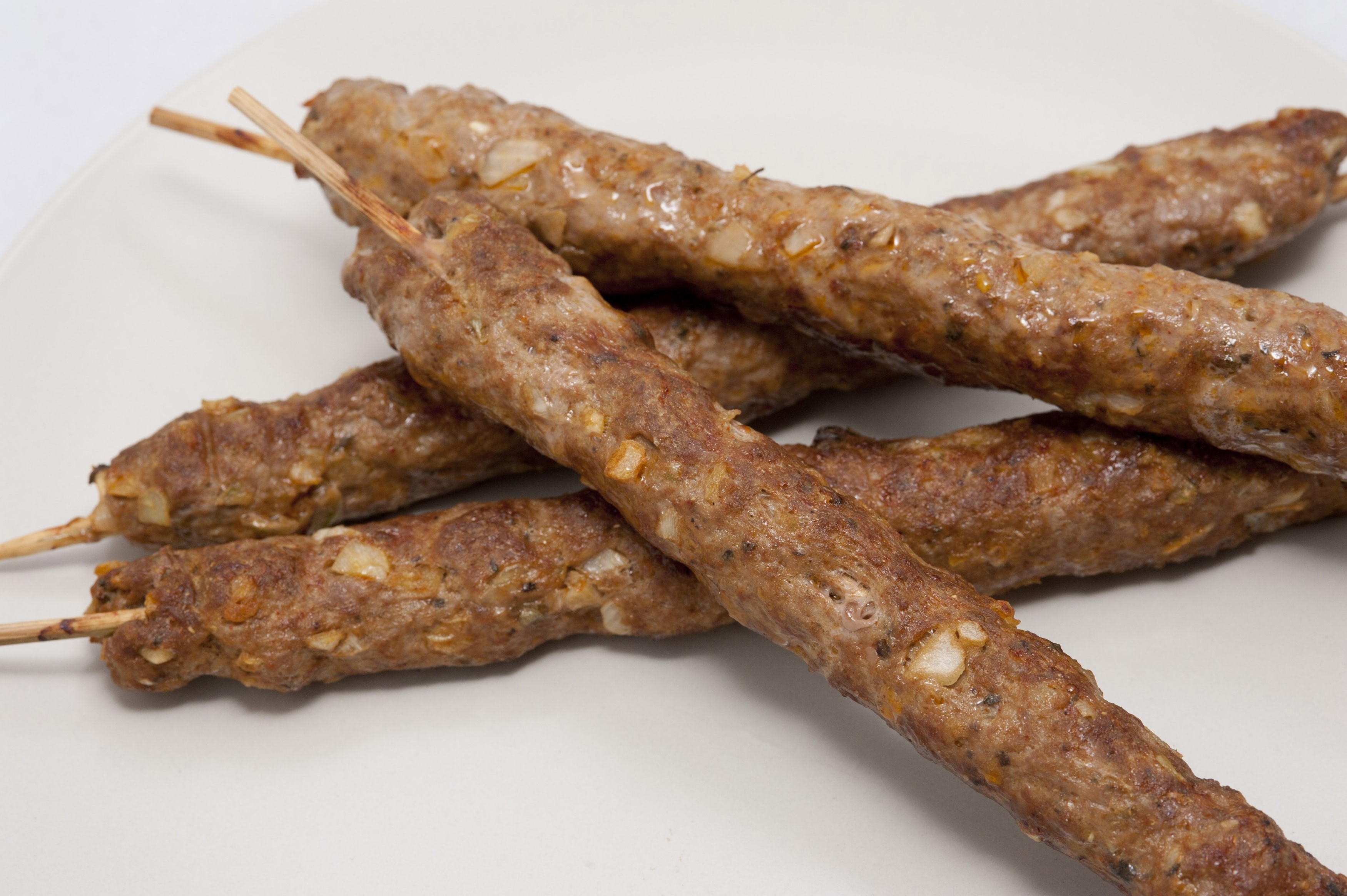 Four delisious grilled kofta lamb kebabs made from spicy minced lamb and cooked on a skewer for a traditional snack