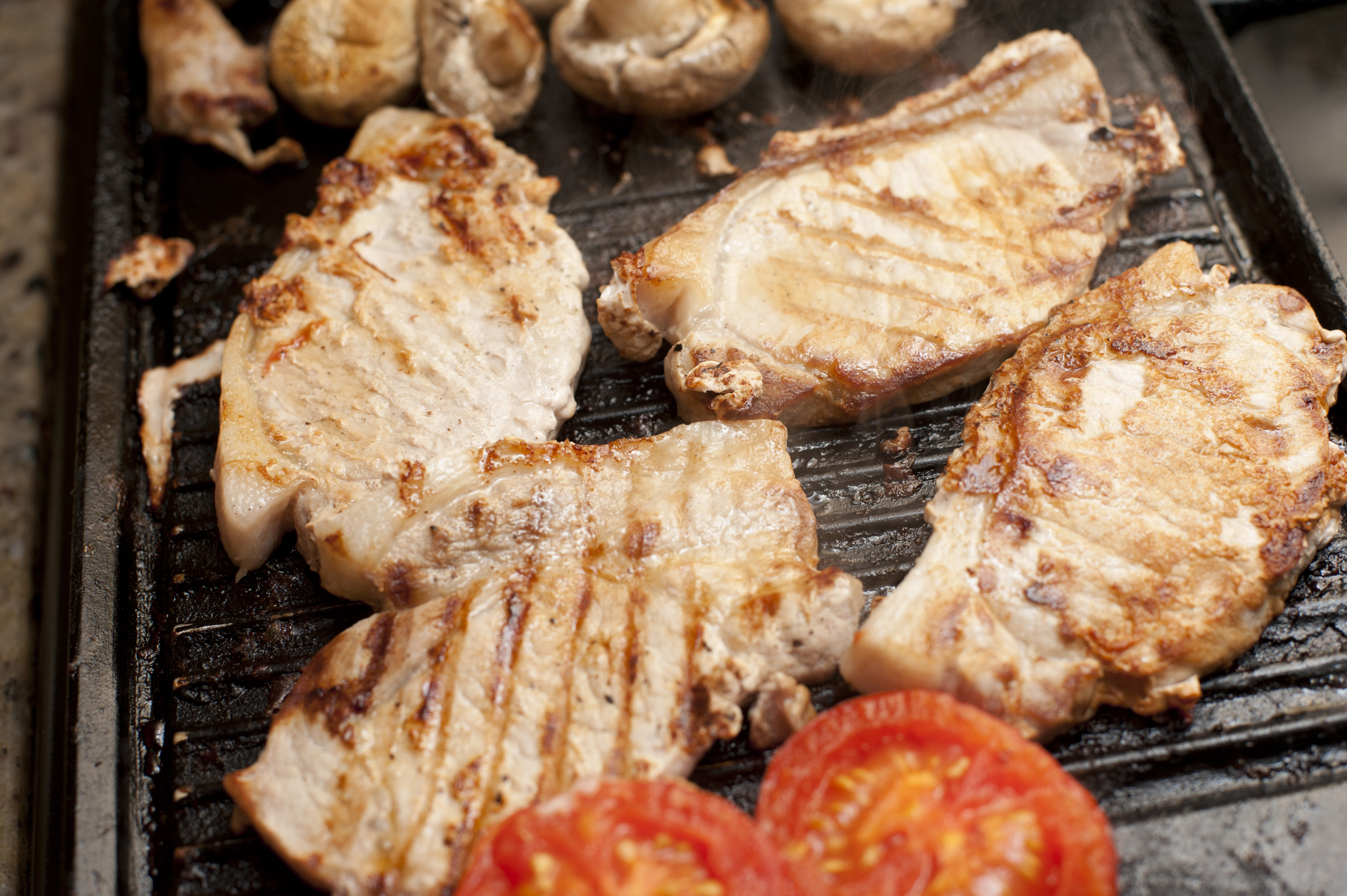 Close-up of four joints of pork grilled with mushrooms and tomatoes
