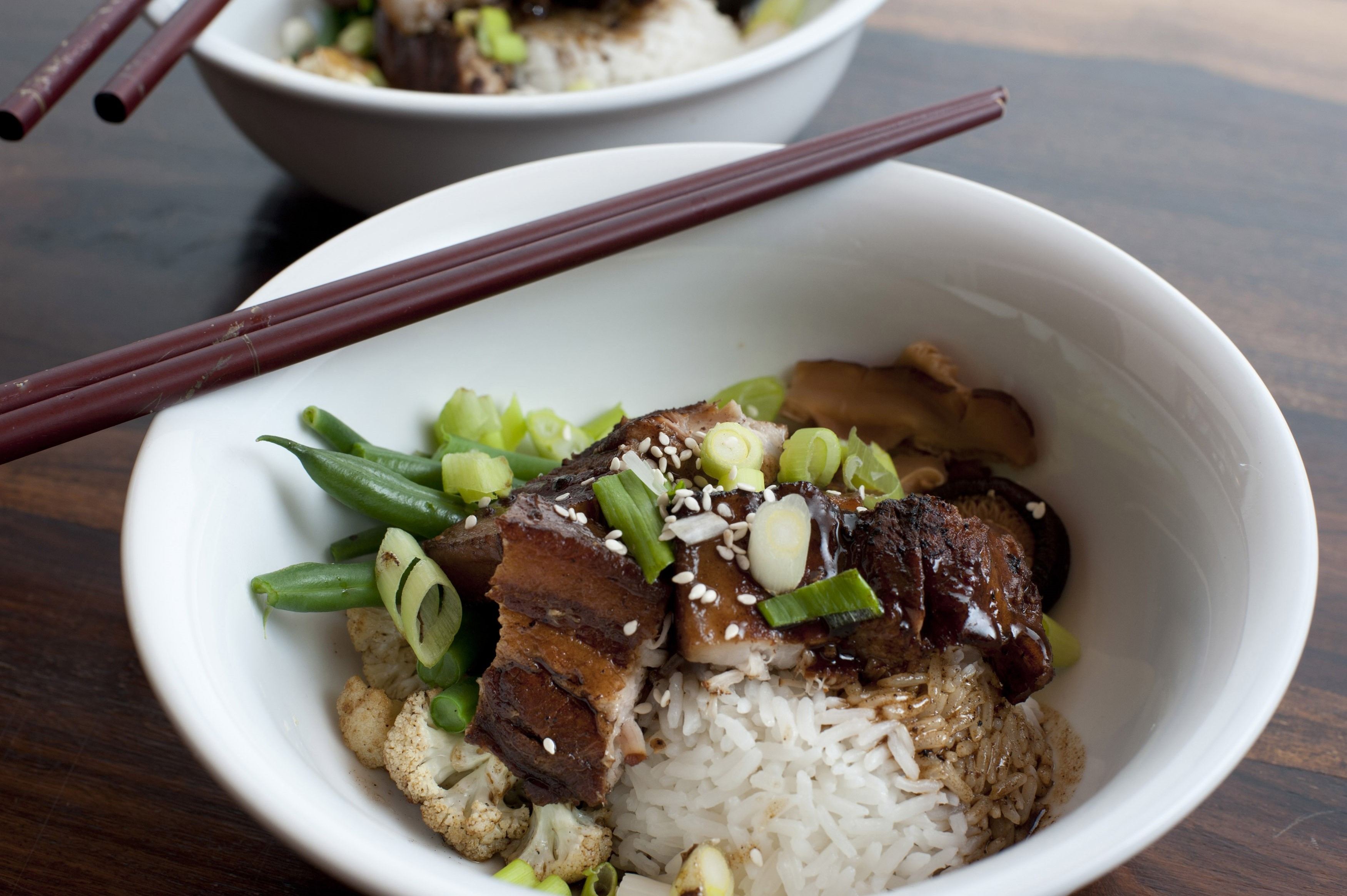 Chinese red pork served in a bowl with rice, cauliflower and beans with chopsticks resting on the rim