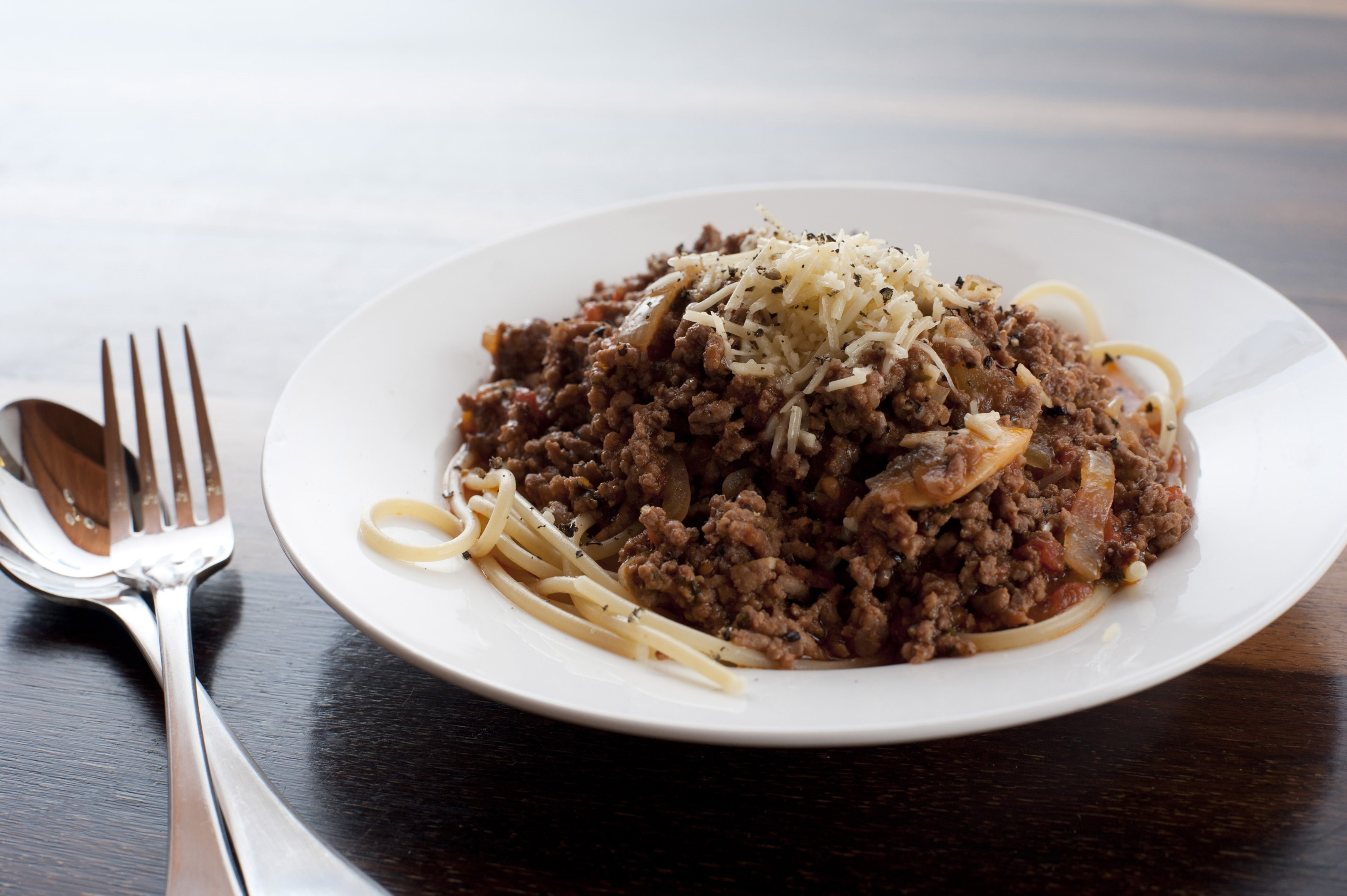 Spaghgetti Bolognese, or Bolognaise, topped with savoury spiced mince meat sprinkled with cheese for healthy Italian cuisine
