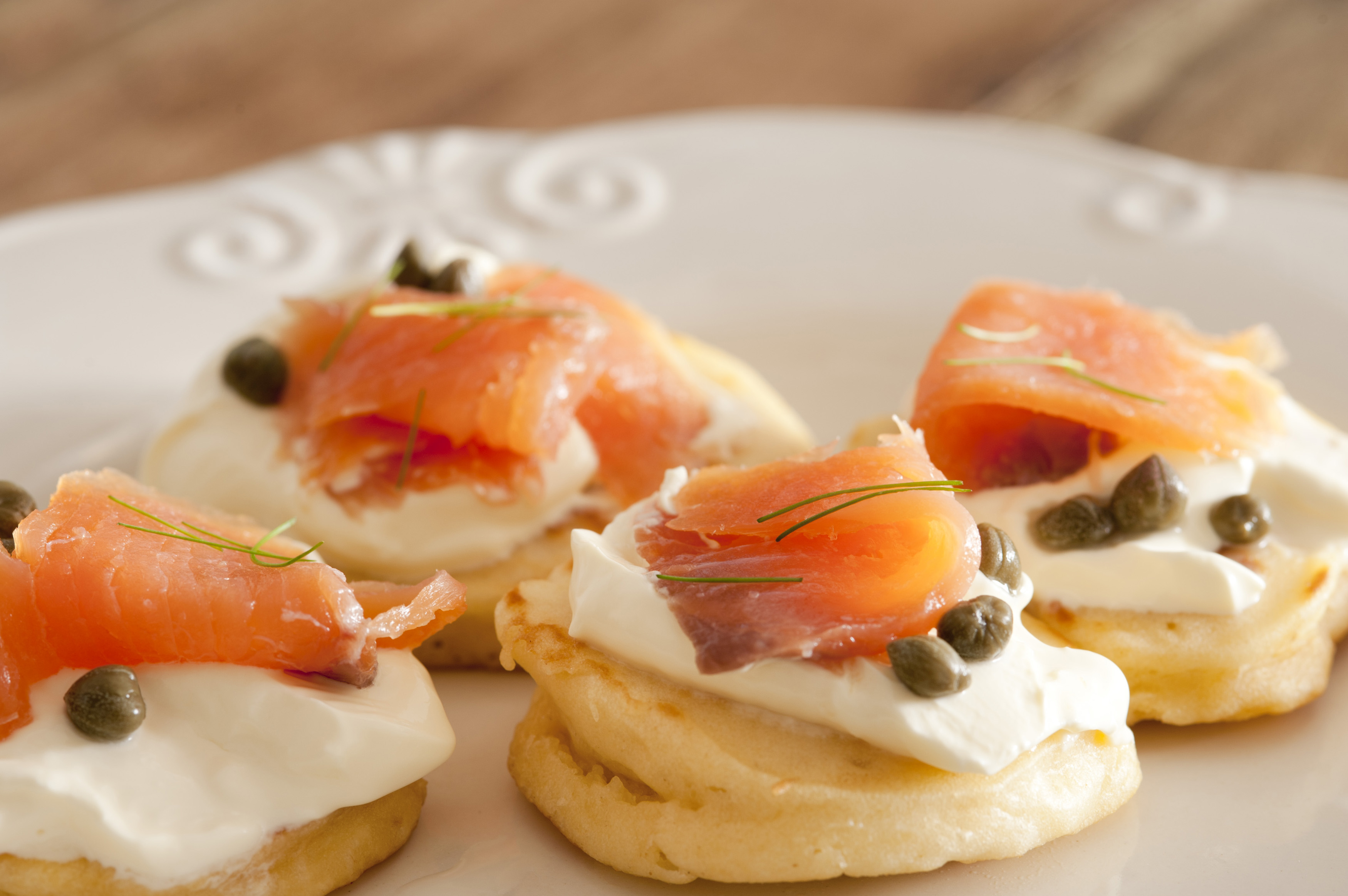 a plate of smoked salmon and cream cheese blini canapes