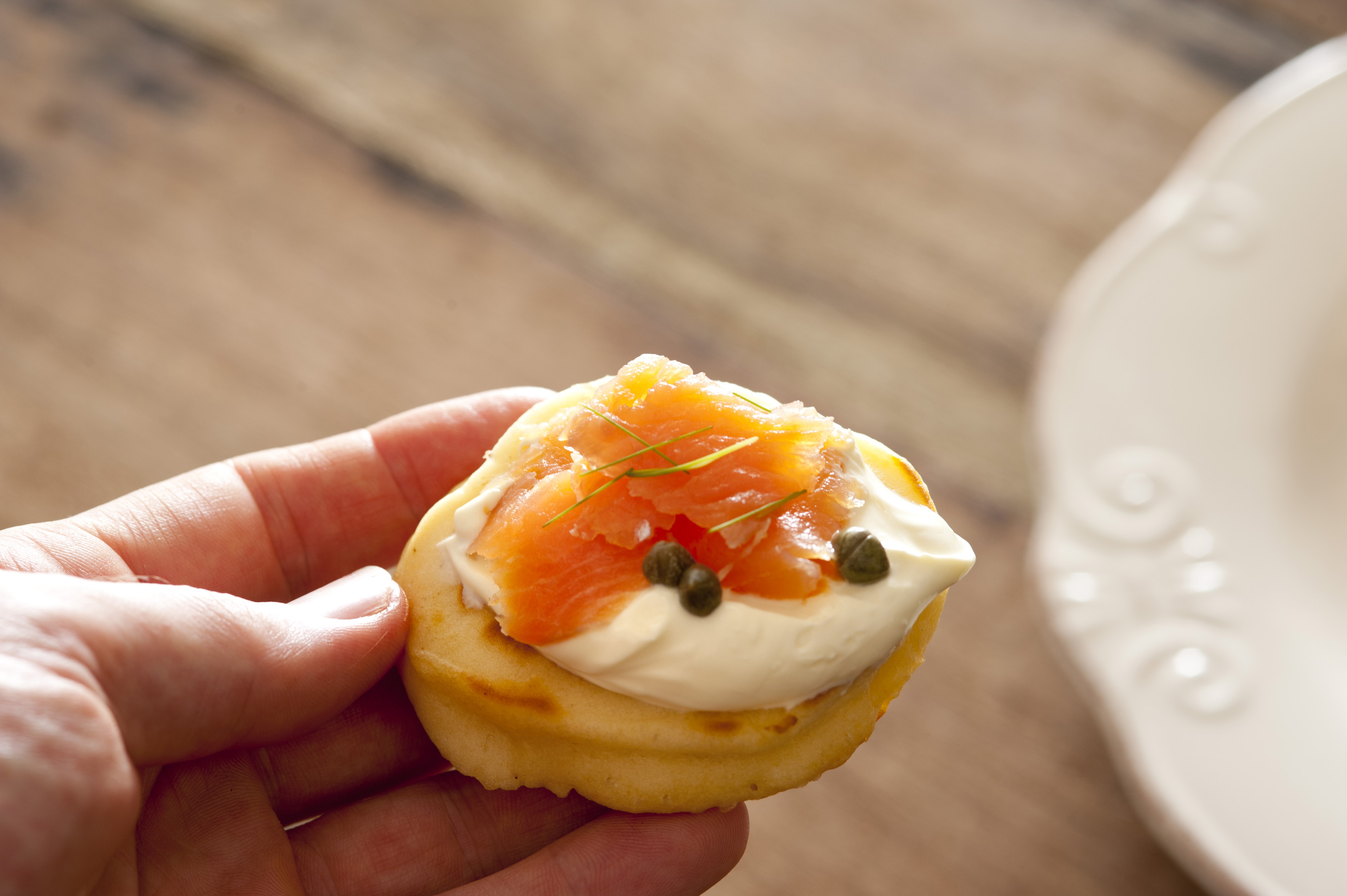 First person view on hand holding delicious blini snack topped with creme and pink salmon over wooden table