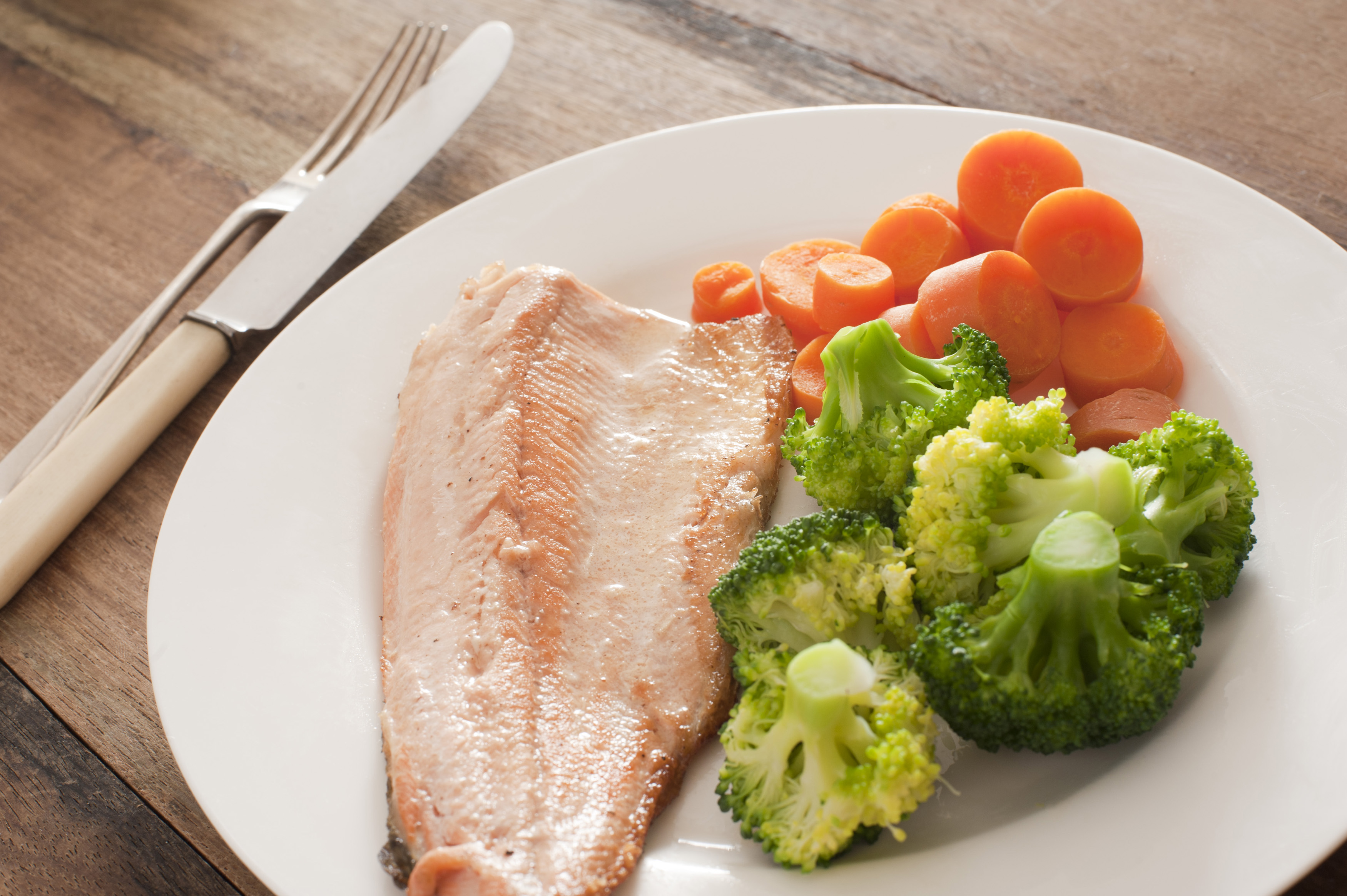 Delicious cooked trout fillet with fresh broccoli and sliced carrots plated on a white plate for a healthy dinner rich in omega-3 fatty acids
