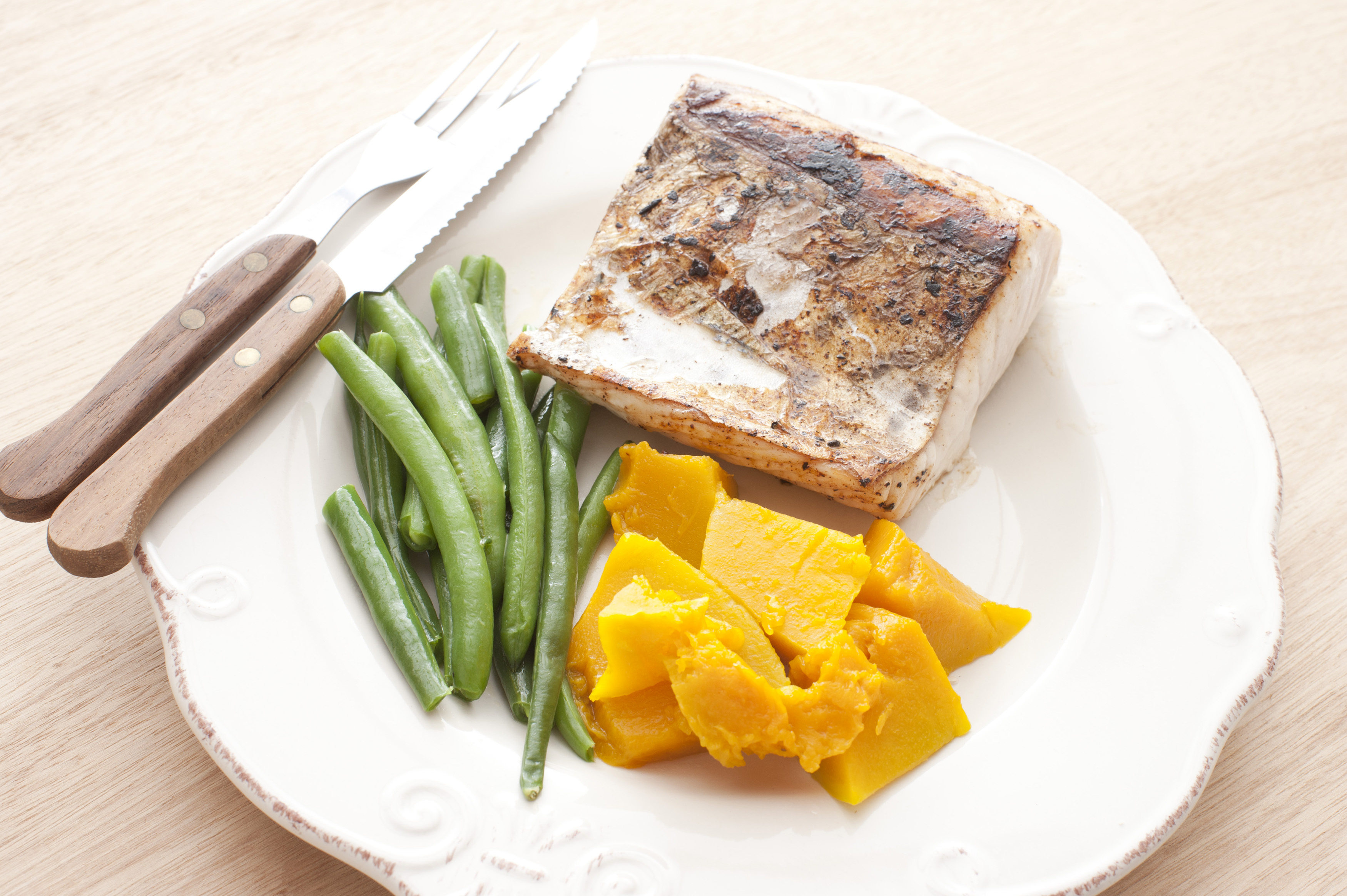 Single square shaped fillet of cooked mackerel, green string beans and yellow squash on plate with fork and knife over wooden table