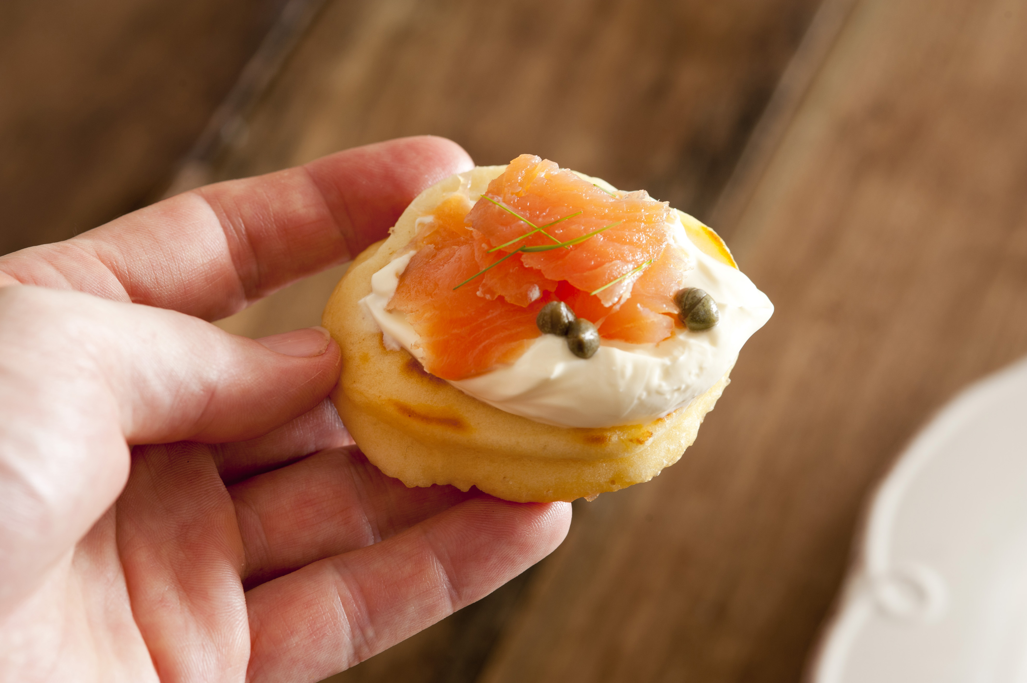 First person view of person eating a blini appetizer with cream, pink salmon and capers in hand