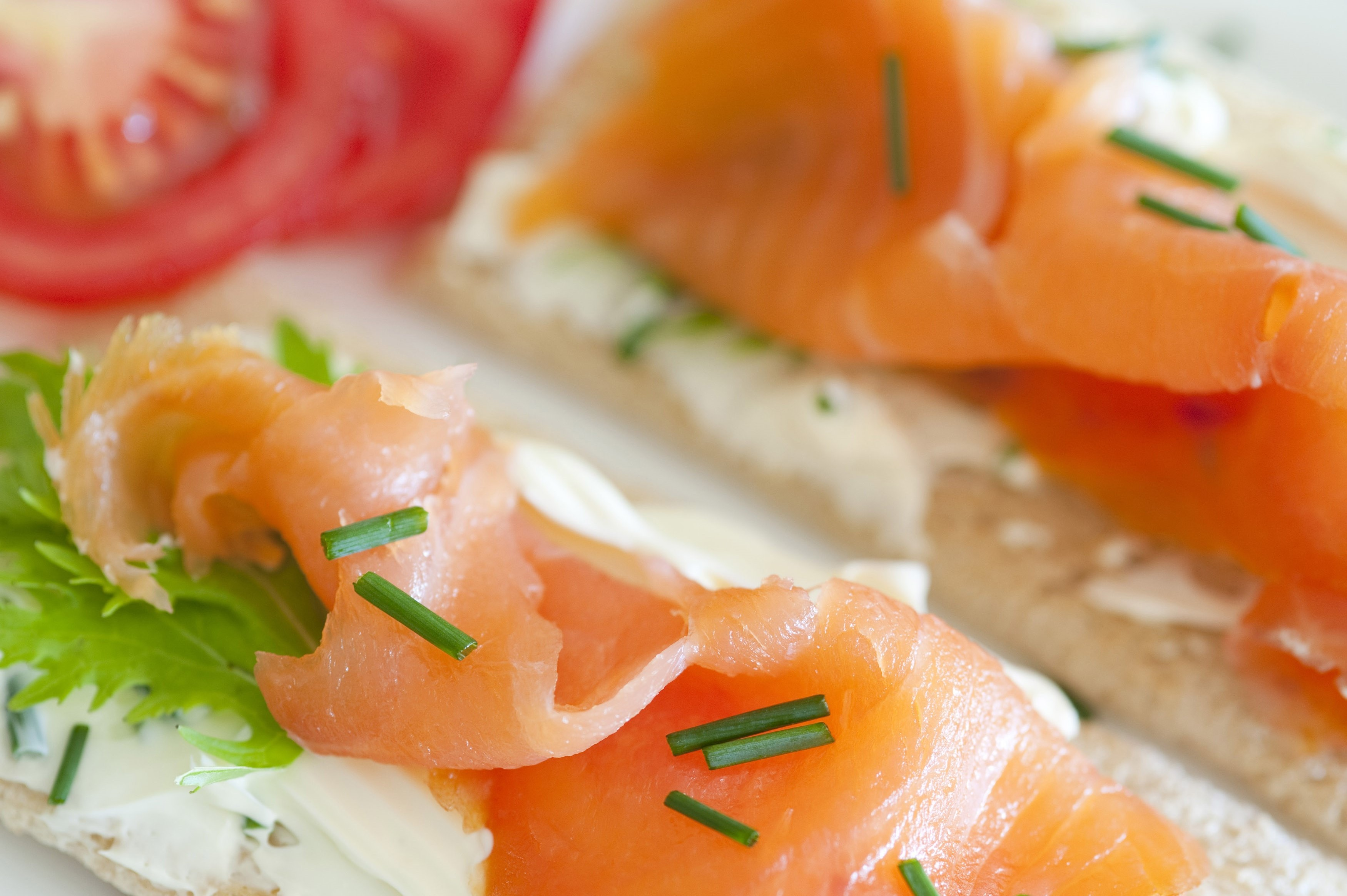 Delicous smoked salmon snack with thinly sliced fish on crispbread topped with fresh chives
