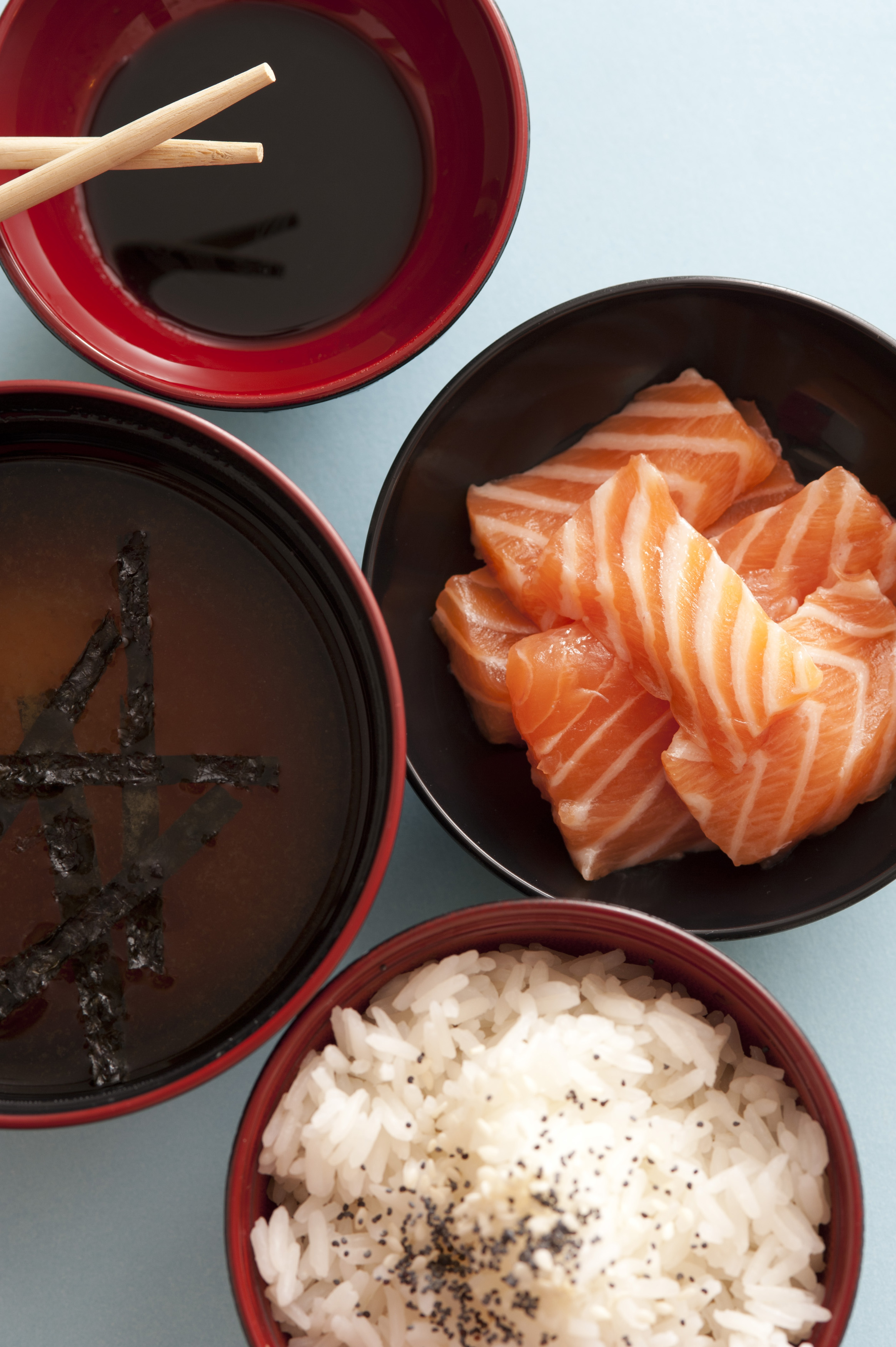 Four bowls of sauce, soup, seasoned white rice and raw fish from first person perspective view