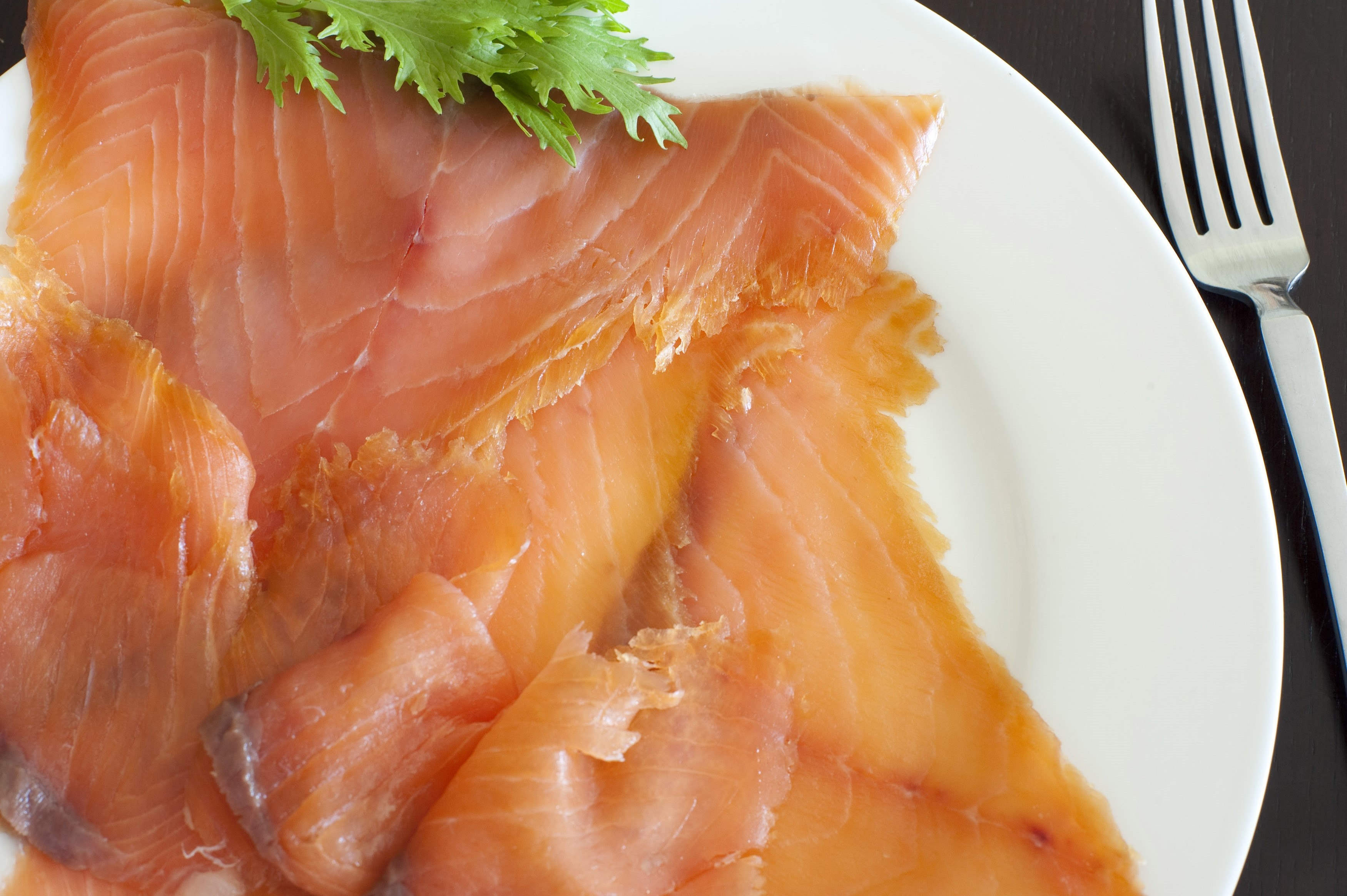 Fresh cured and smoked salmon slices served on a plate for a gourmet seafood dinner, close up overhead view