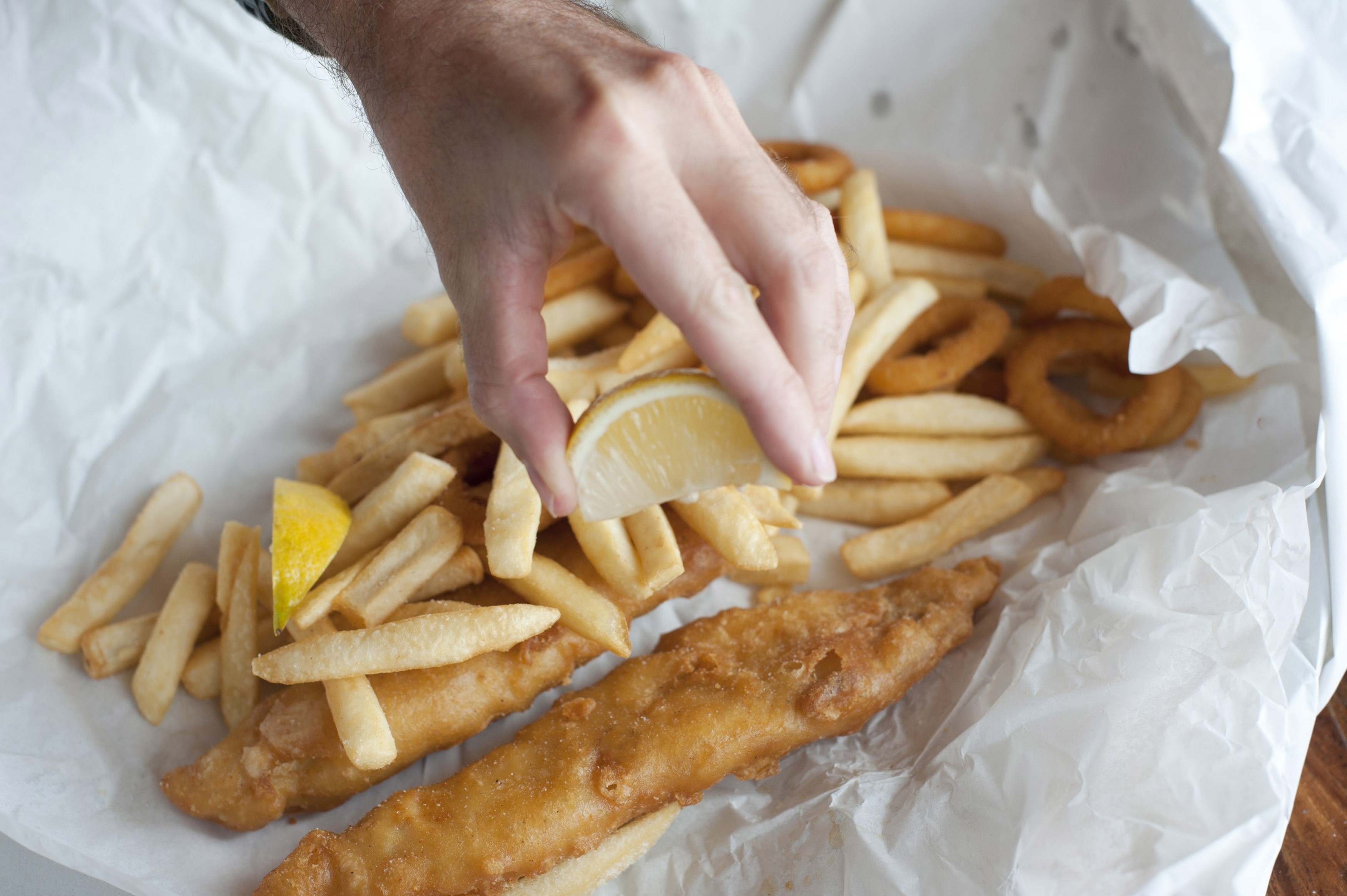 Hand squeezing lemon over takeaway fried fish fillets and calamari in batter with fried potato chips on crumpled paper