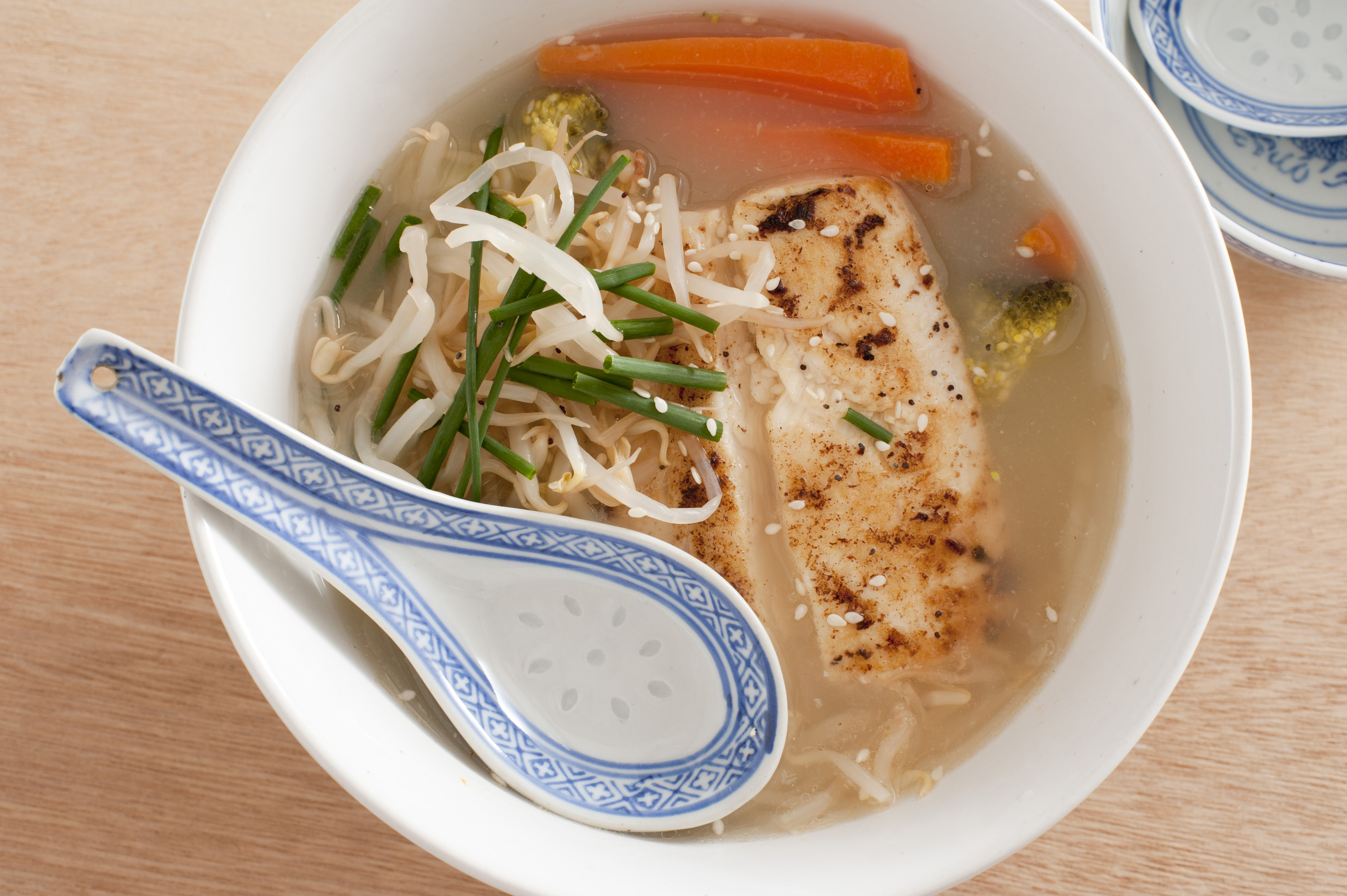 Above view on ornate spoon in bowl of Thai fish with chives, bean sprouts and carrot slices