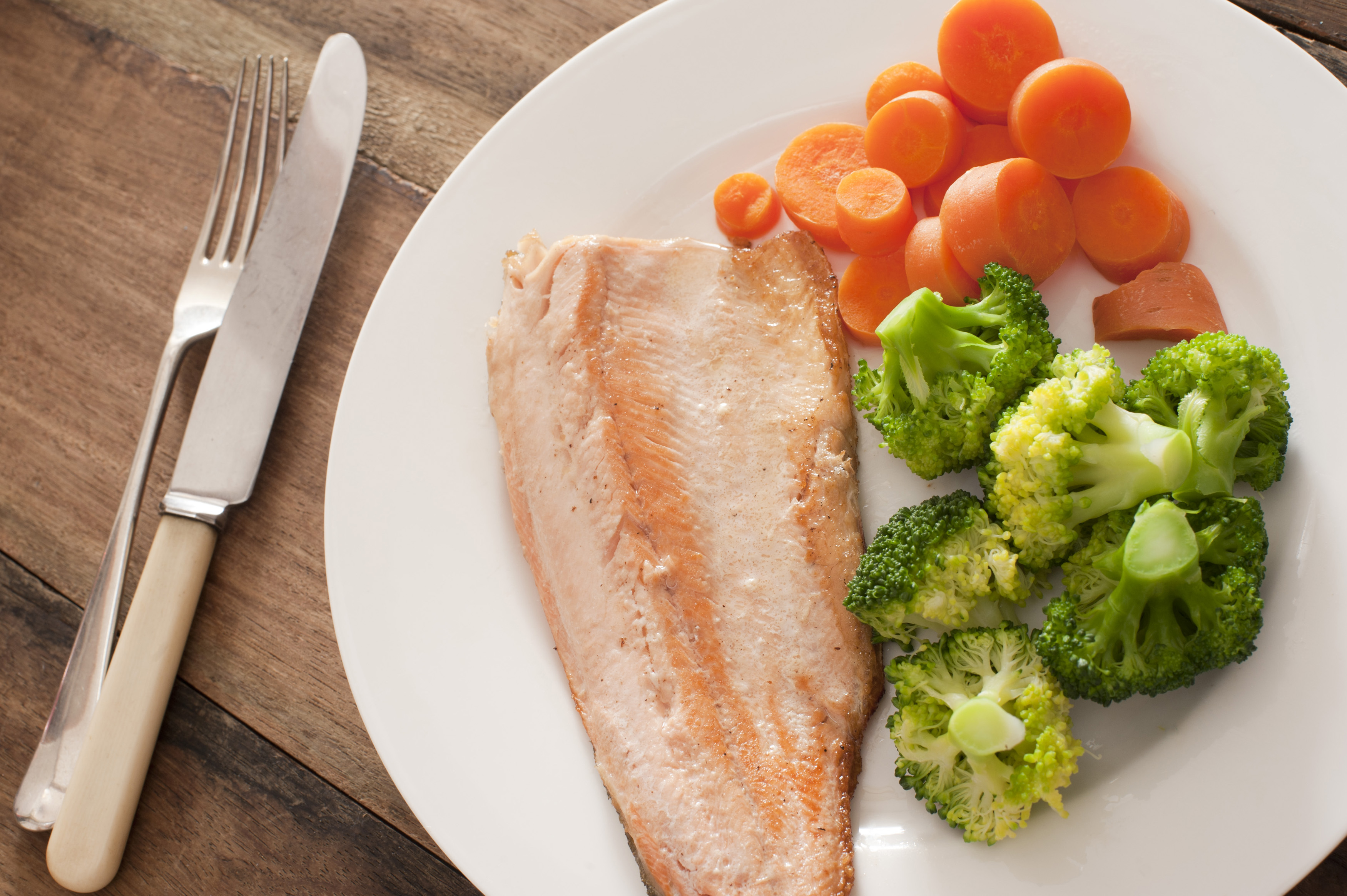 First person perspective view over single round plate of cooked trout dinner with green broccoli and slices of carrots next to fork and knife over wooden table