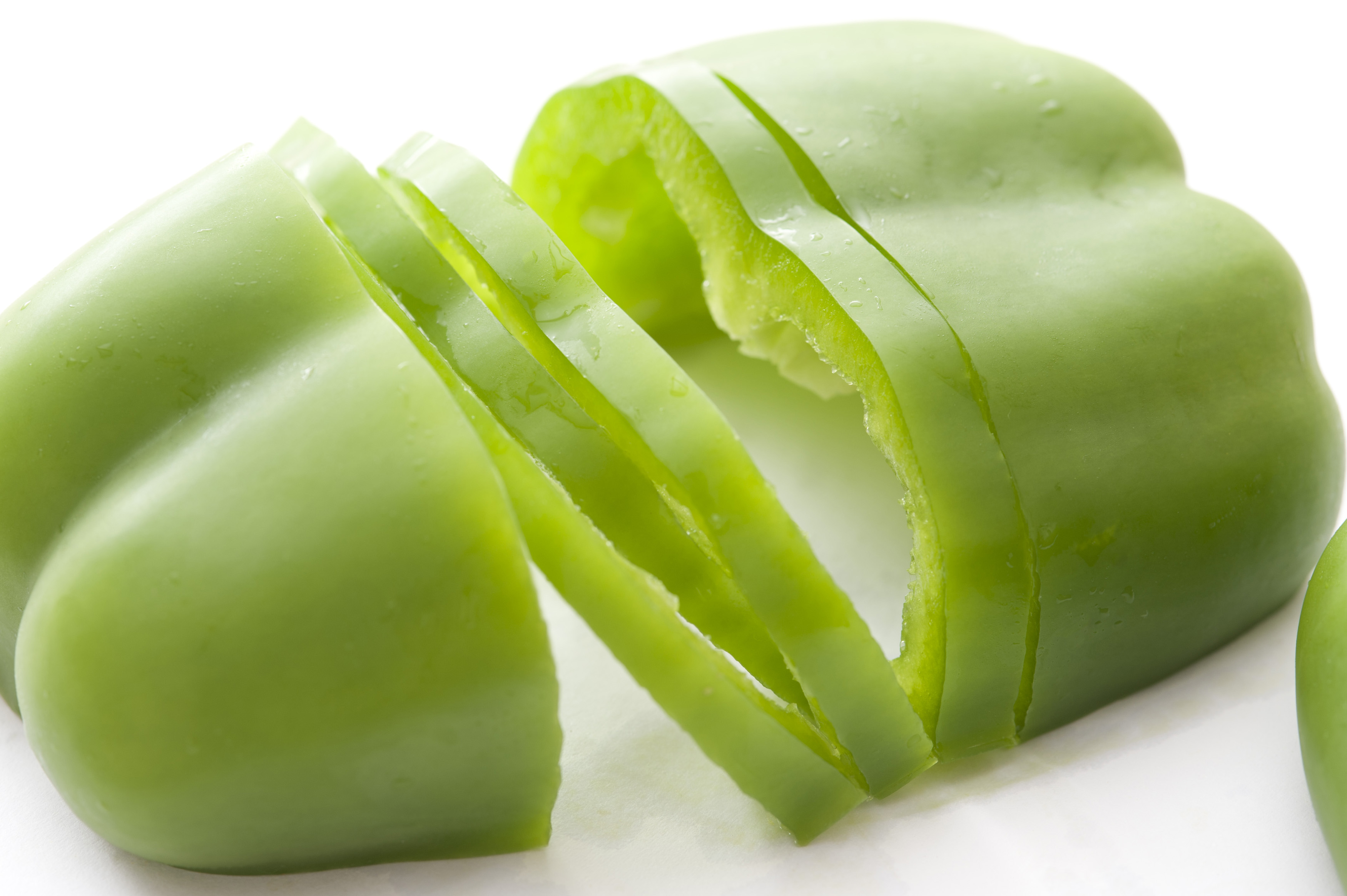 Halved and sliced fresh green sweet bell pepper or capsicum for use as an ingredient in a salad or for cooking