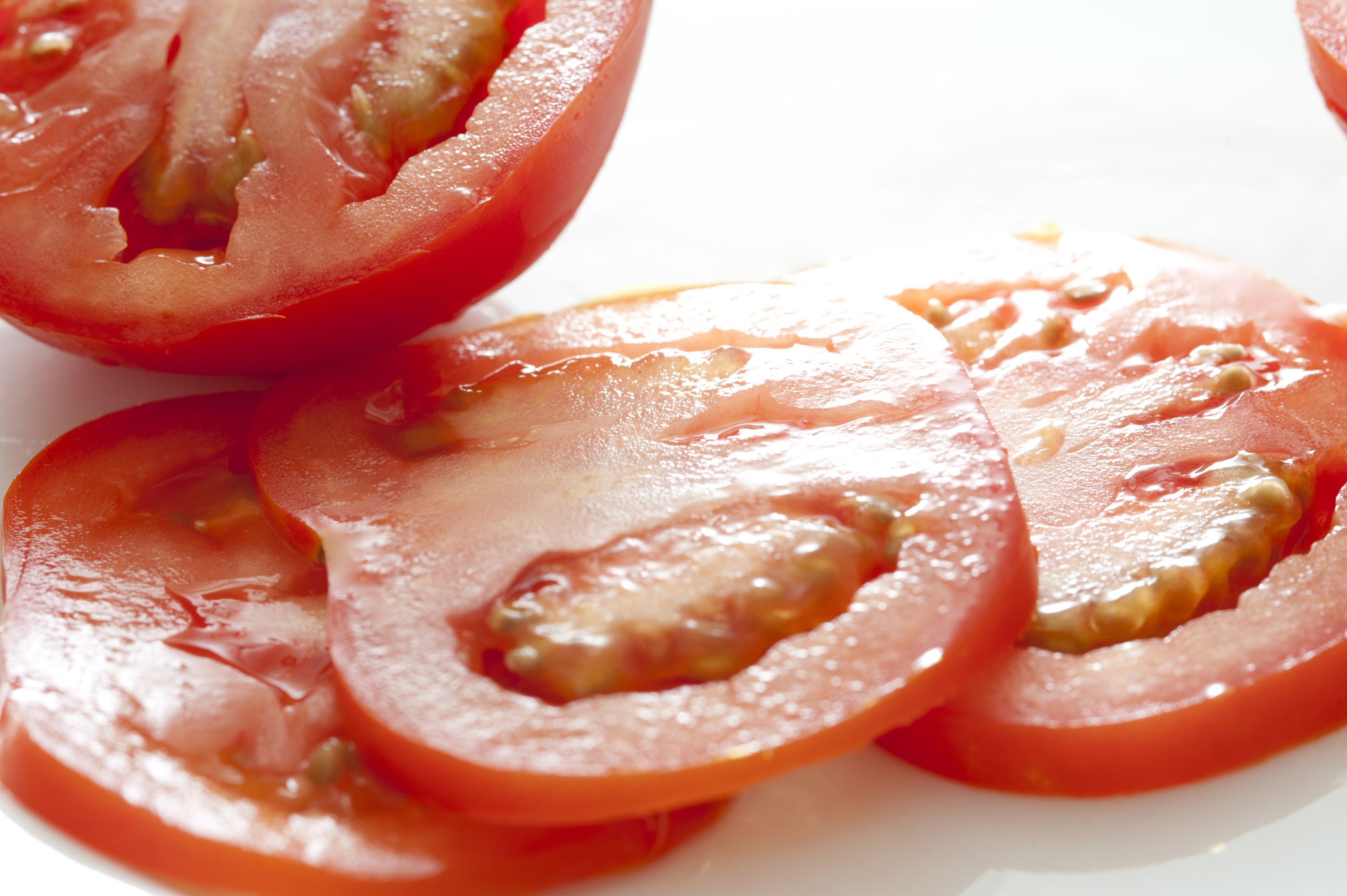 Slices of fresh ripe red tomato lying on a white background in front of a halved juicy tomato, close up view