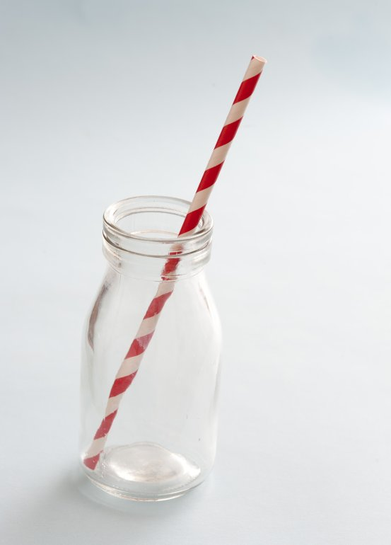 Glass Milk Bottle With Striped Straw Free Stock Image